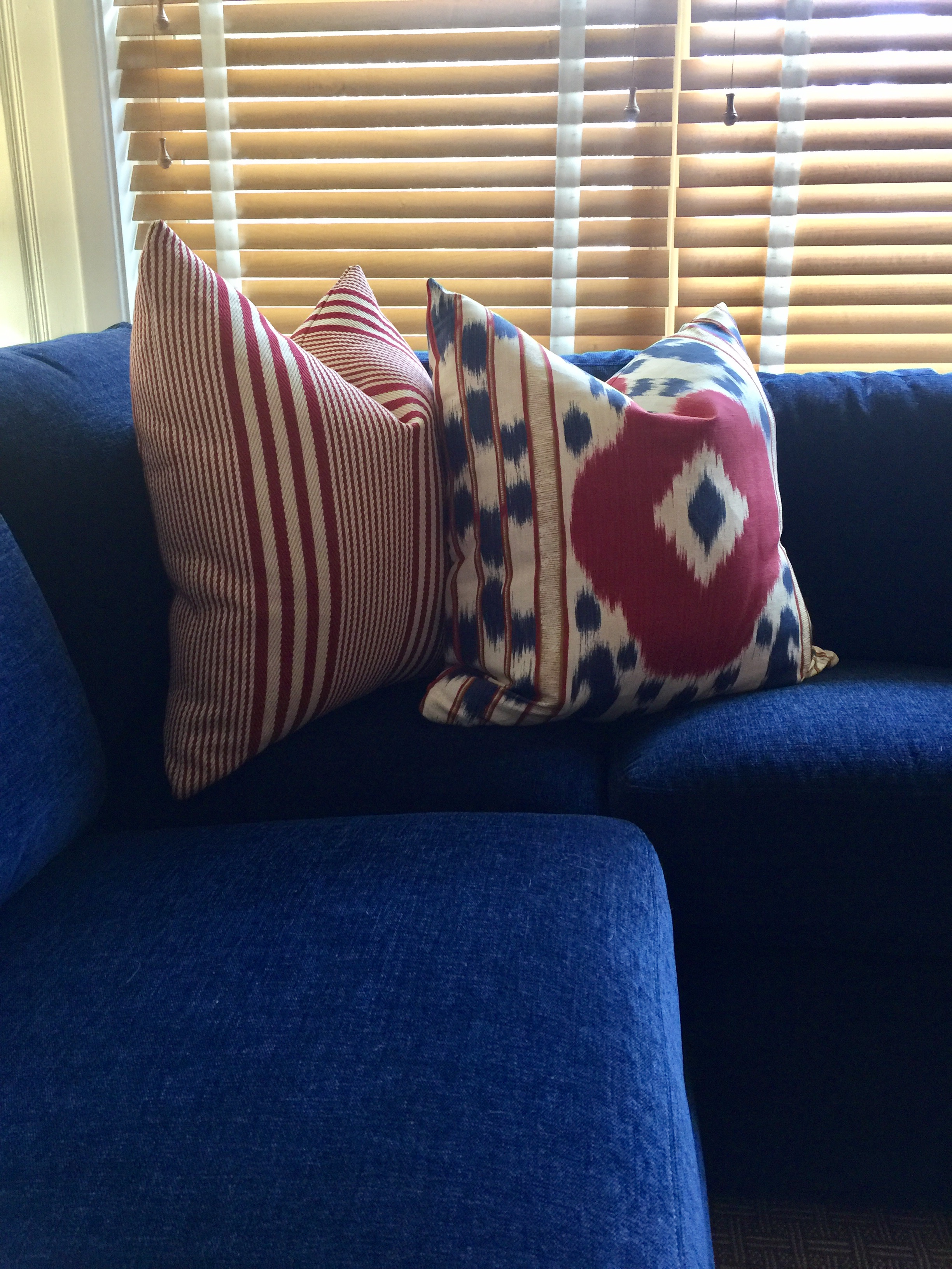 Blue sofa with red white and blue pillows and wood blinds - Designer: Carla Aston