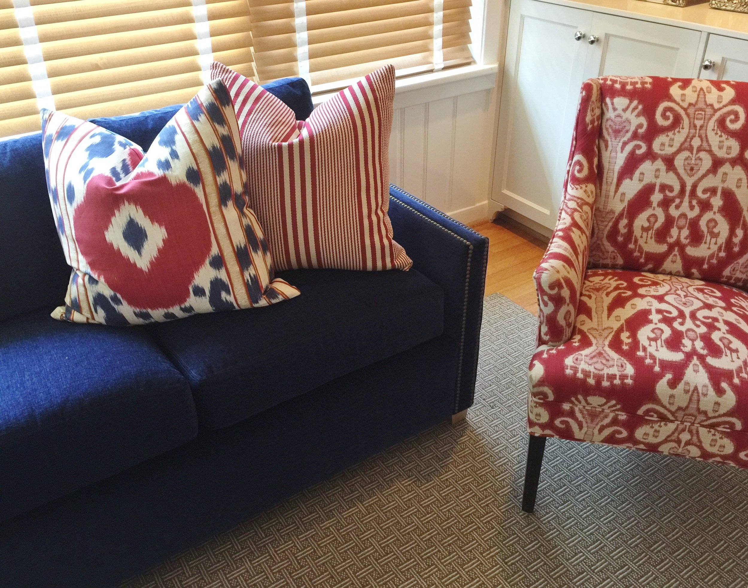 Blue sectional sofa with red, white, and blue pillows
