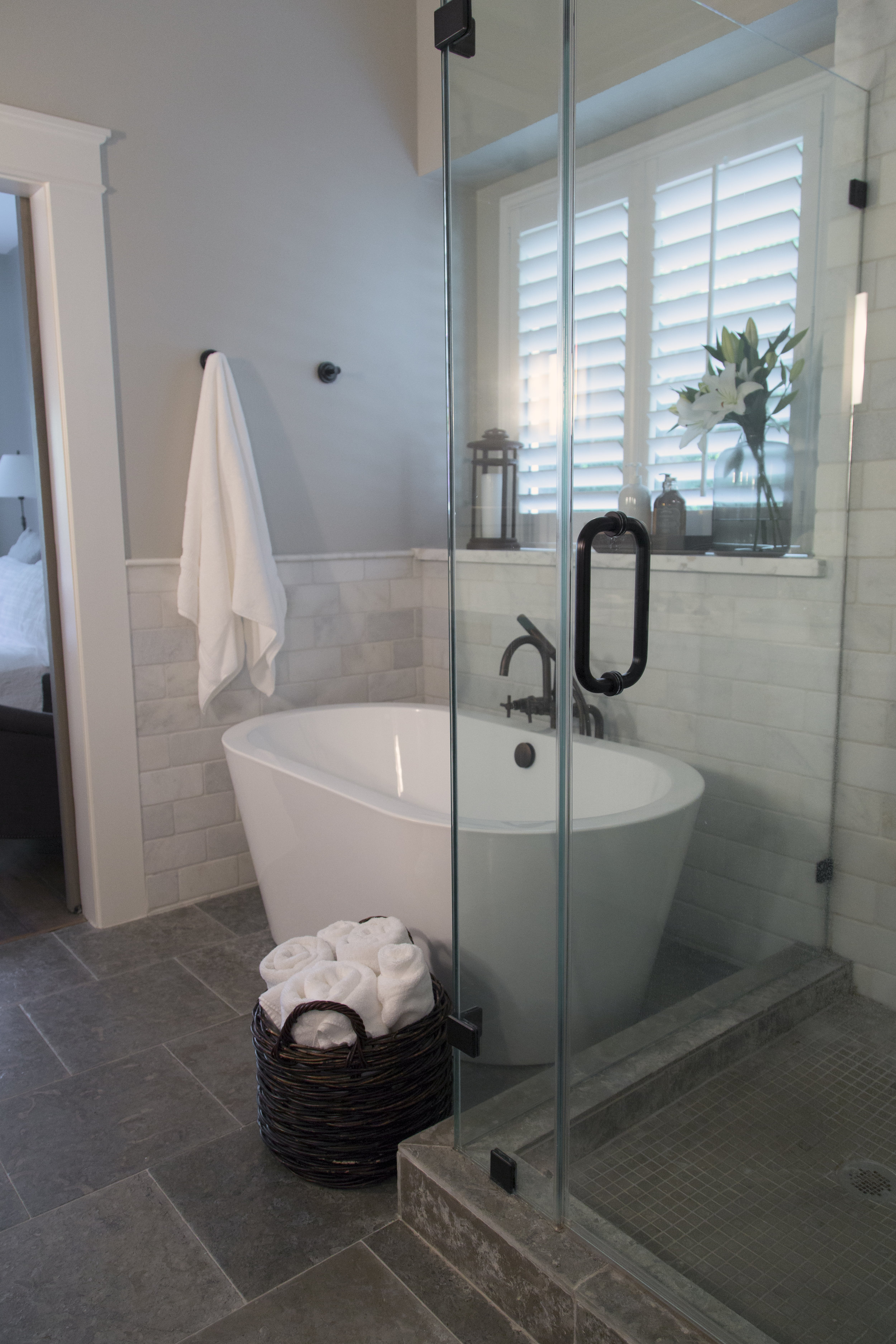 The same type limestone tile we used on the floor was used in the shower stall, just in a smaller size, to get a continuous look and expand the look of this bathroom. Wall tile flows from shower walls to surround tub as well. Designer Carla Aston, Photo by Tori Aston