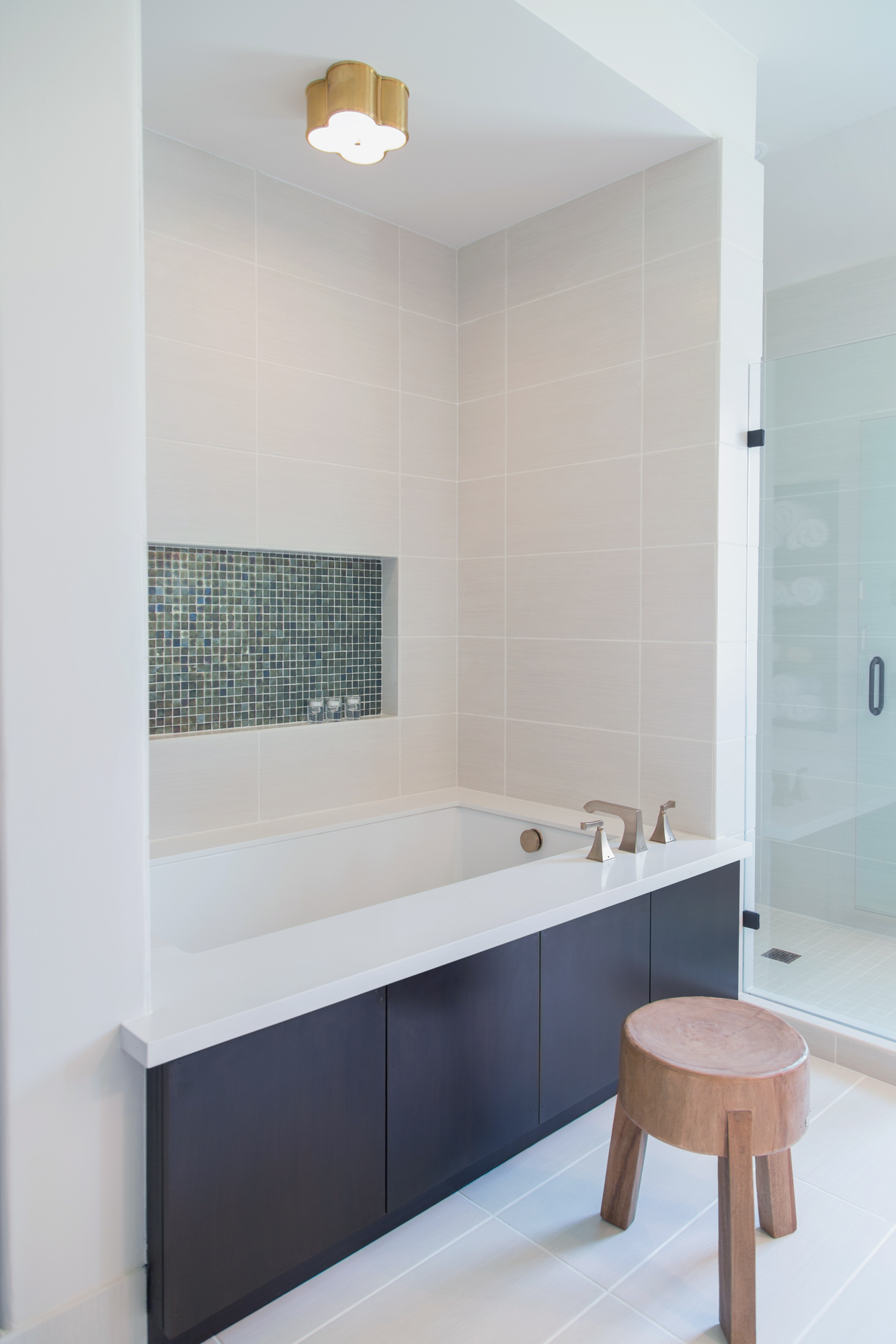Here, the shower tile wraps the corner and flows into the area around the tub too, making for a more seamless look. Carla Aston Designer, Tori Aston Photographer