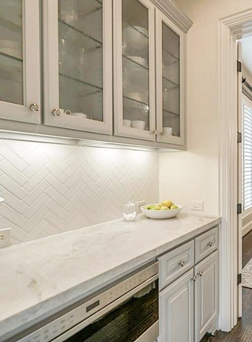 After - updated Butler's pantry with gray cabinets, Taj Mahal quartzite, herringbone tile backsplash and undercounter microwave drawer. - Carla Aston Designer