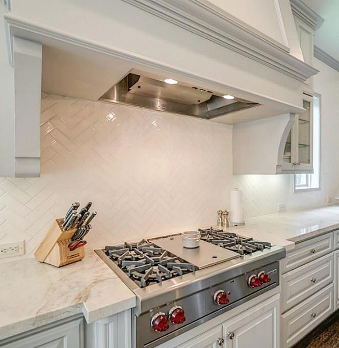 After kitchen remodel with new Taj Mahal countertops, herringbone backsplash, gray cabinets - Carla Aston Designer
