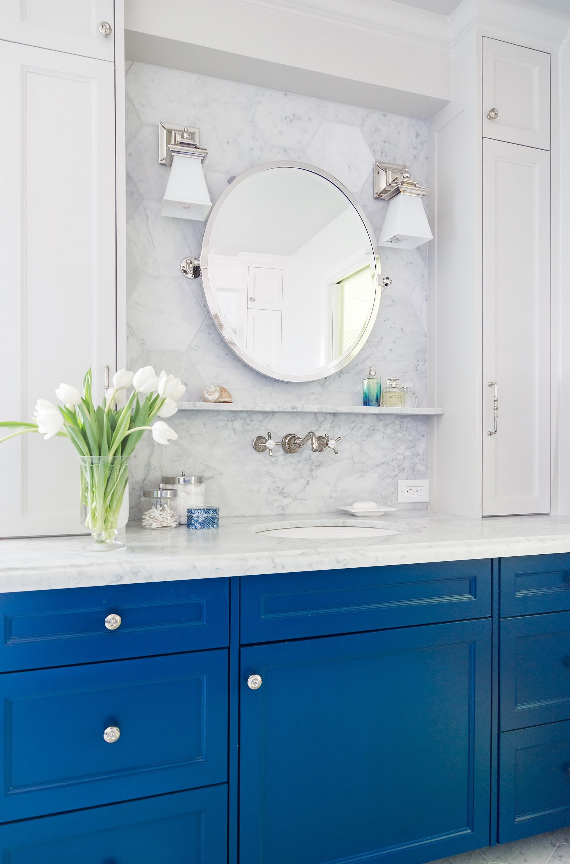 Blue lower cabinetry with Carrara marble in bathroom remodel | Carla Aston, Designer | Tori Aston, Photographer  #bathroomremodel #marblebathroom #hextile #bluecabinets