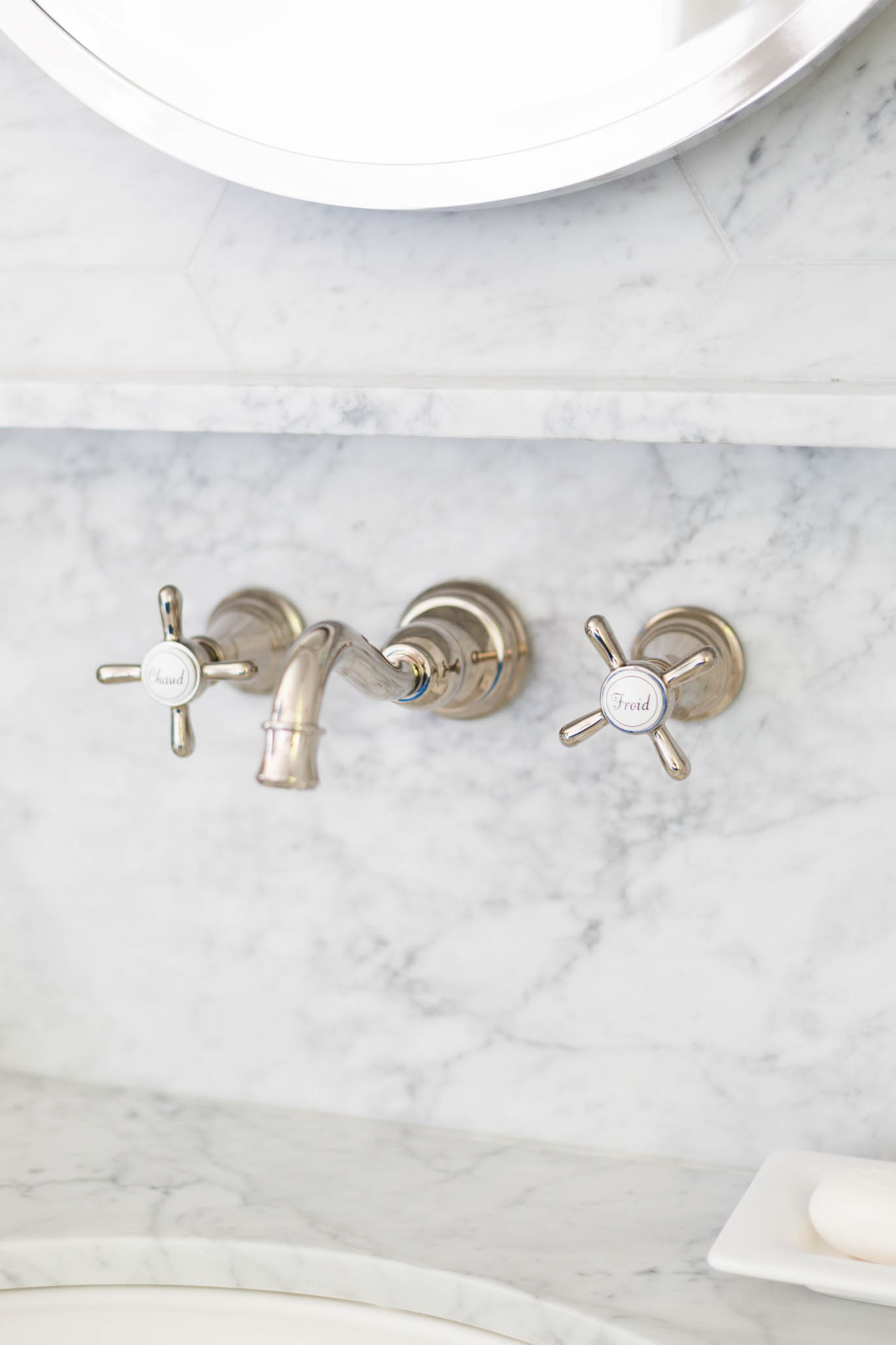 Wall mount faucet on white marble backsplash with ledge at bathroom sink | Carla Aston, Designer | Tori Aston, Photographer  #bathroomremodel #marblebathroom #hextile