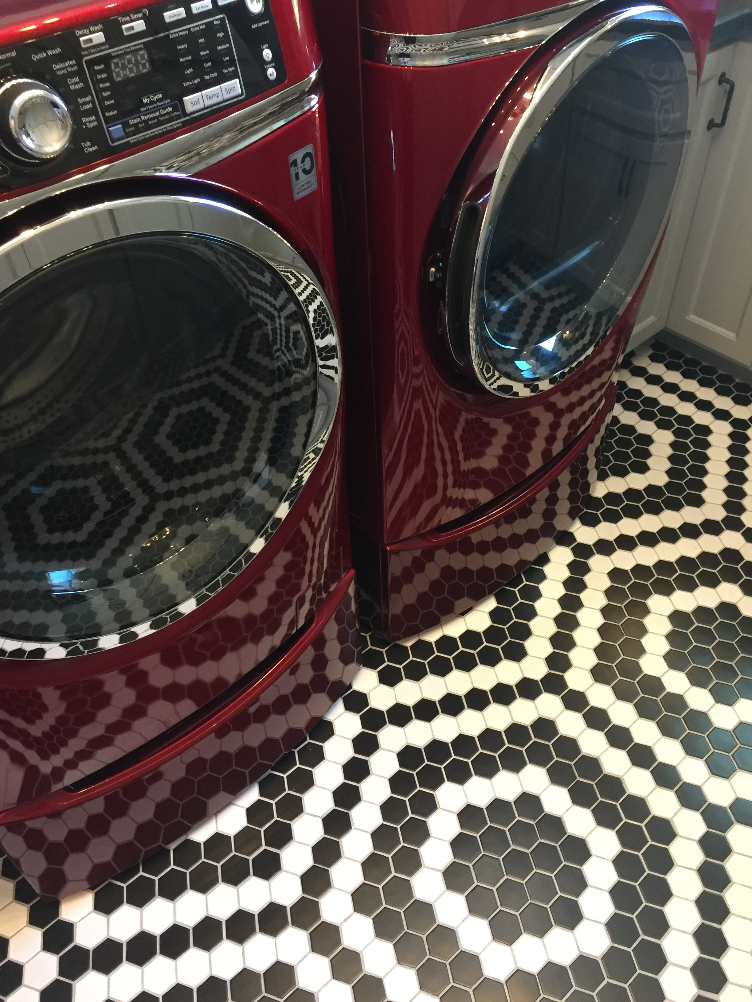 Southern Living Showcase Home - laundry room with red appliances and black and white tile floor, Designed by Chairma Design Group #blackandwhite #tilefloor #blackandwhitefloor
