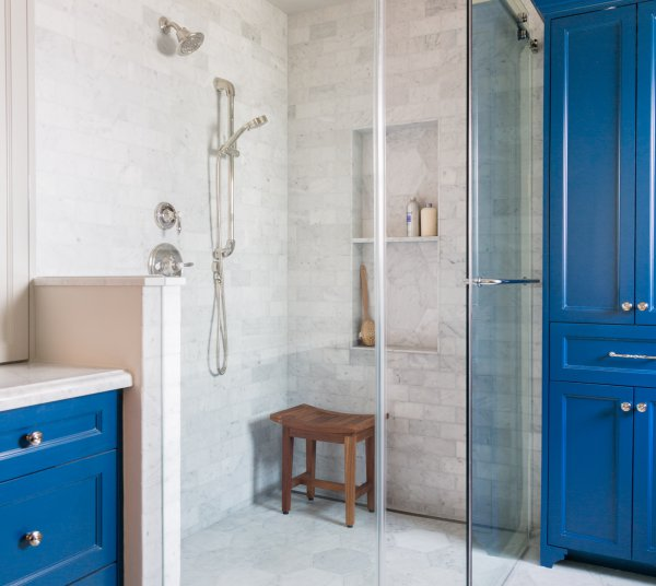 Master bath shower with white Carrara marble and blue cabinets, Designer: Carla Aston
