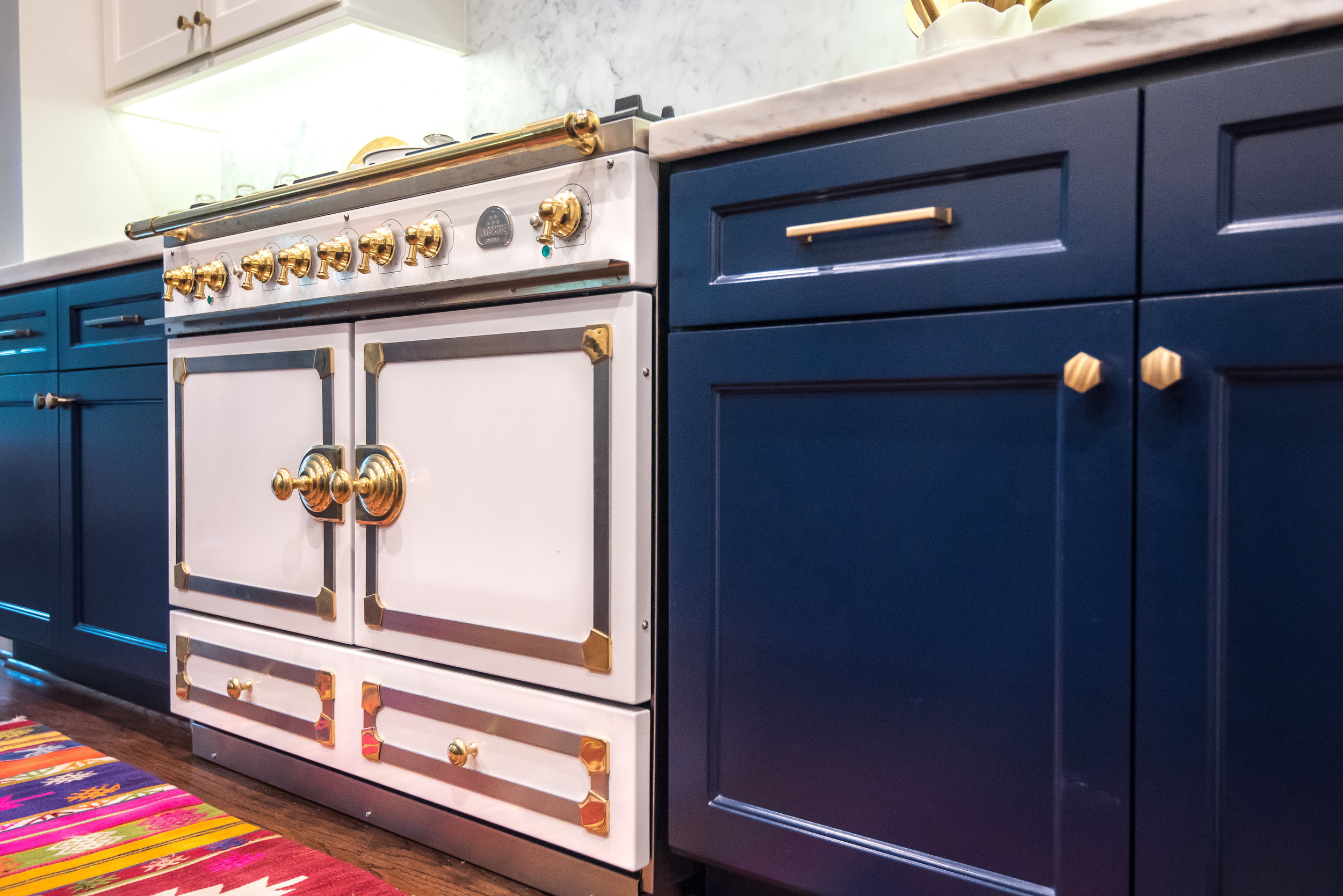 Navy and white kitchen with white marble counters, Designer: Carla Aston