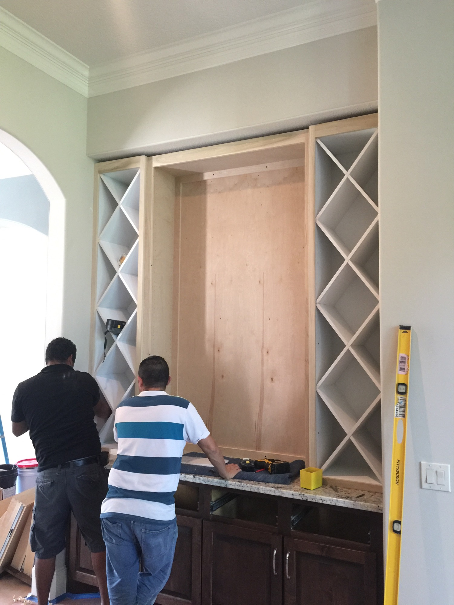 Progress shot - new upper cabinetry with wine racks added for the bar area #remodel #winerack