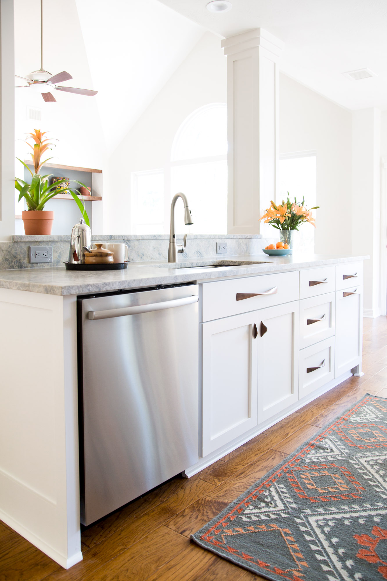Simple white kitchen remodel with quartzite countertops, wood floors, and wood cabinet pulls | Carla Aston, Designer | Tori Aston, Photographer #whitekitchen #midcenturystyle #quartzitecountertops #kitchenremodel #kitchenremodelideas