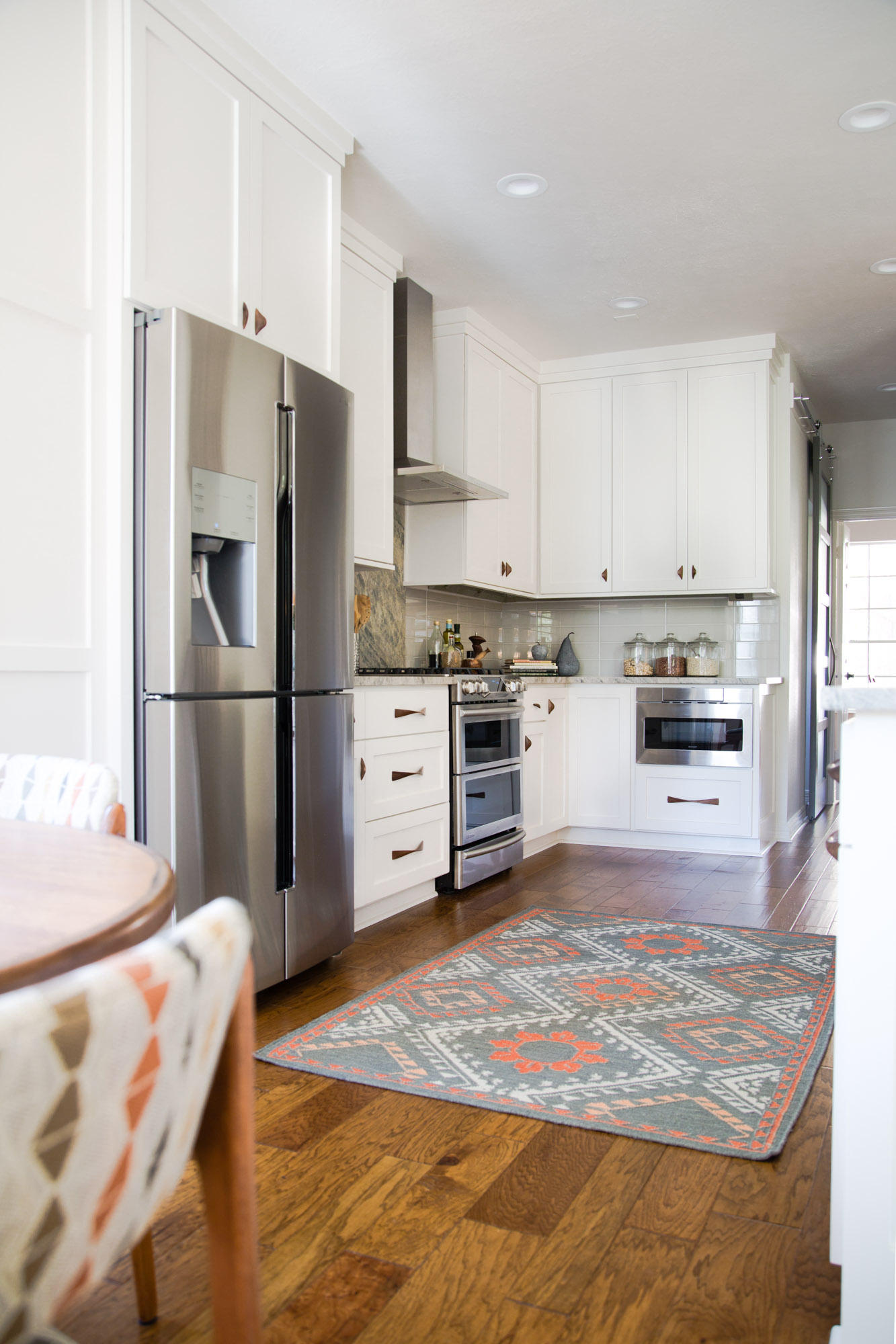 Simple white kitchen remodel with quartzite countertops, wood floors, and wood cabinet pulls | Carla Aston, Designer | Tori Aston, Photographer #whitekitchen #midcenturystyle #quartzitecountertops #kitchenremodel #kitchenremodelideas #kitchenrug