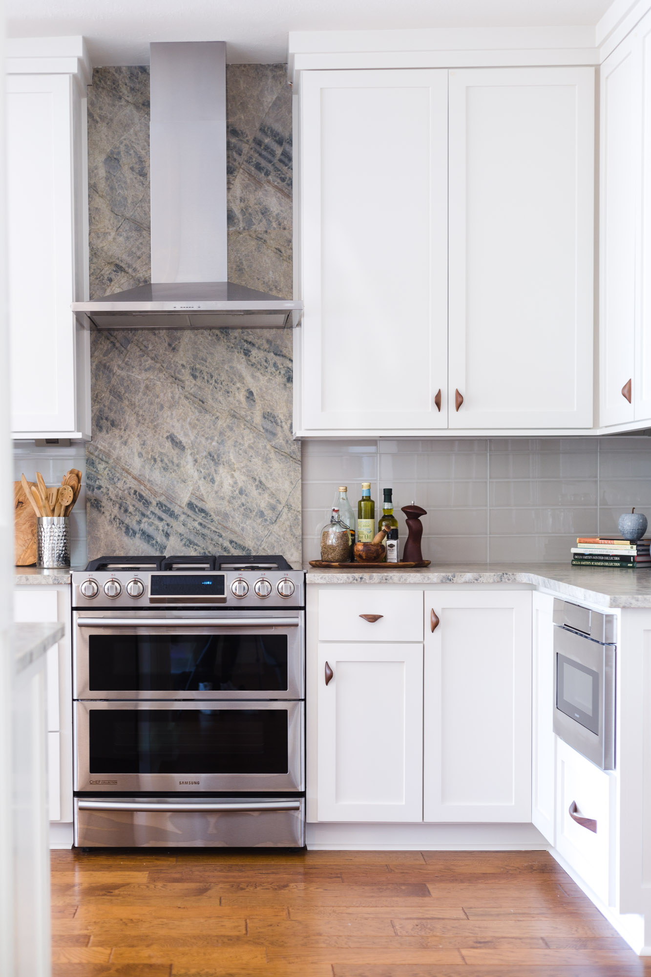 Simple white kitchen remodel with quartzite countertops, wood floors, and wood cabinet pulls | Carla Aston, Designer | Tori Aston, Photographer #whitekitchen #midcenturystyle #quartzitecountertops #kitchenremodel #kitchenremodelideas #venthood #drawermicrowave
