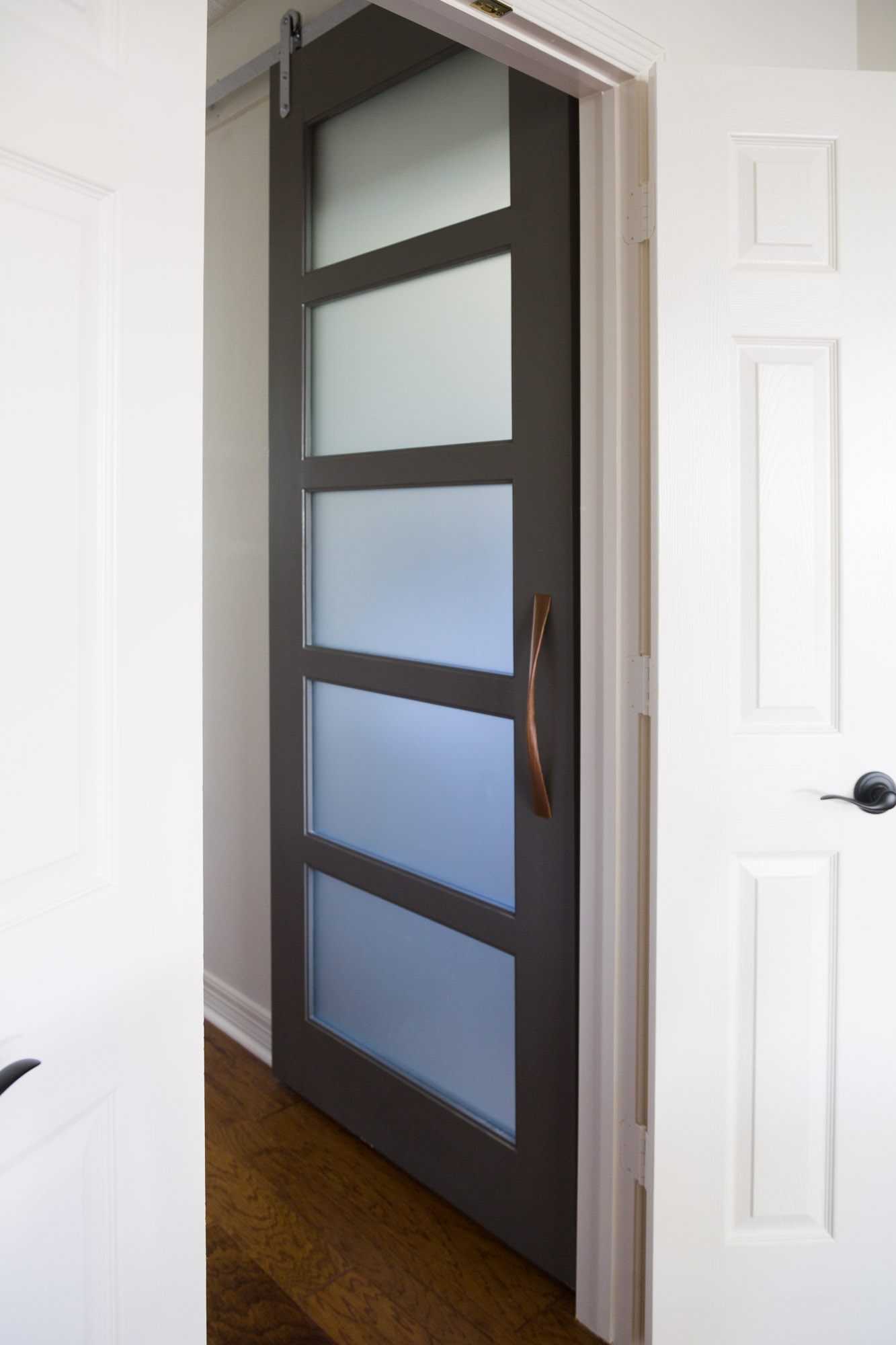 New barn door at laundry room that kept door swing out of that crowded space and provided a nice detail in this hallway. See more about  this job at this link.  | Interior Design Trends For The New Year! #interiordesigntrends #remodelingtrends #barndoor