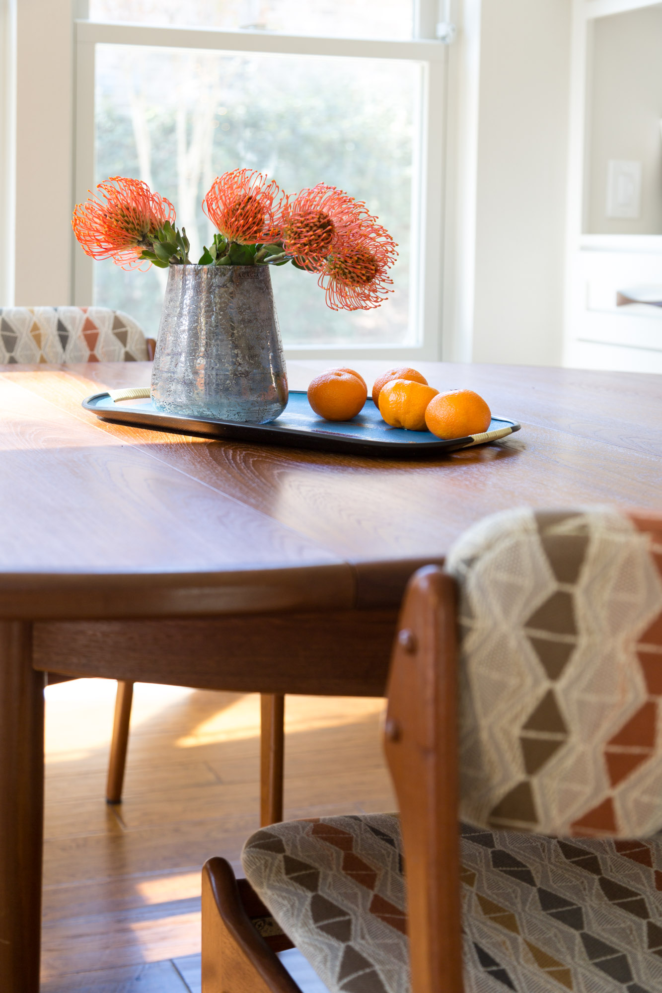 Mid century modern table and chairs in breakfast room with orange pincushion flowers, Designer: Carla Aston