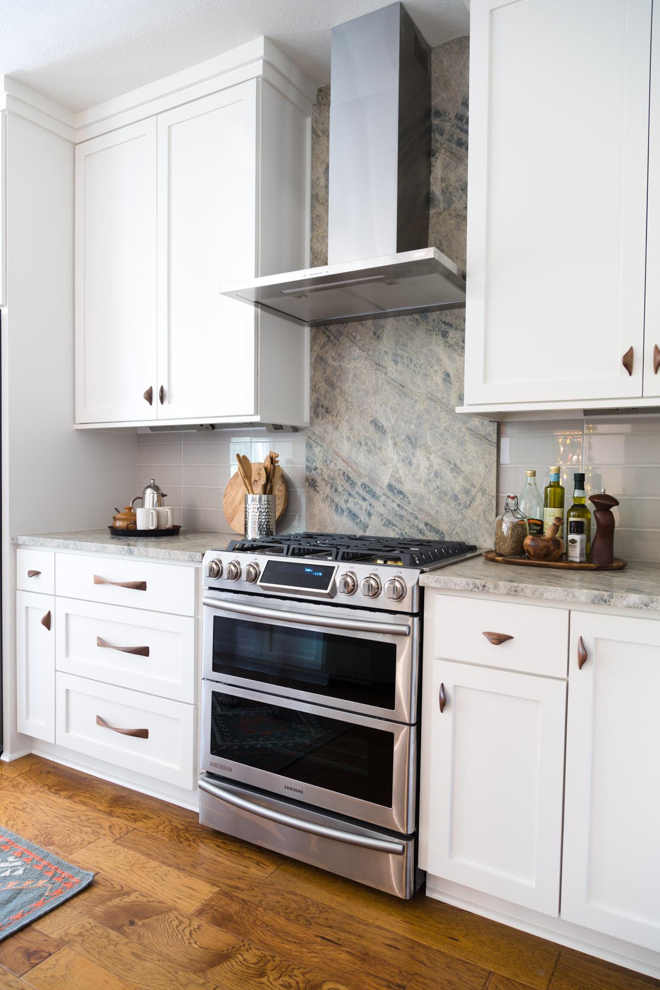 Kitchen remodel with white cabinets, quartzite countertop and splash, wood cabinet pulls, Designer: Carla Aston