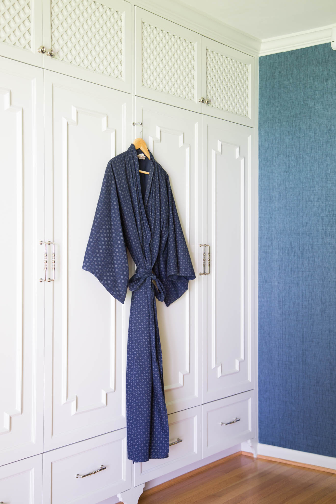 Mouldings and trim details were added to the face of these wardrobe style closet doors to create a chinoiserie styling. Designer: Carla Aston, Photographer: Tori Aston #mouldings #wardrobestylecloset #cabinetry #interiordesigntips