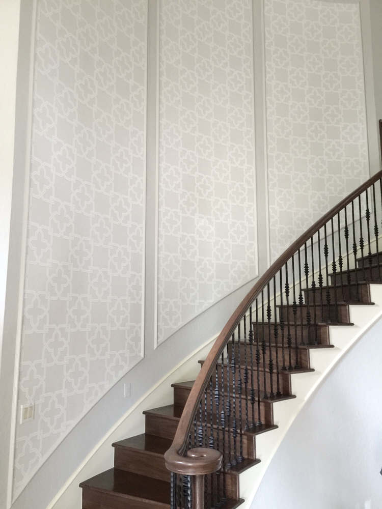 AFTER - With fresh paint and wallcovering added after the mouldings, this wall has a whole new look! Designer: Carla Aston #mouldings #wallpaper #stair #walldecor