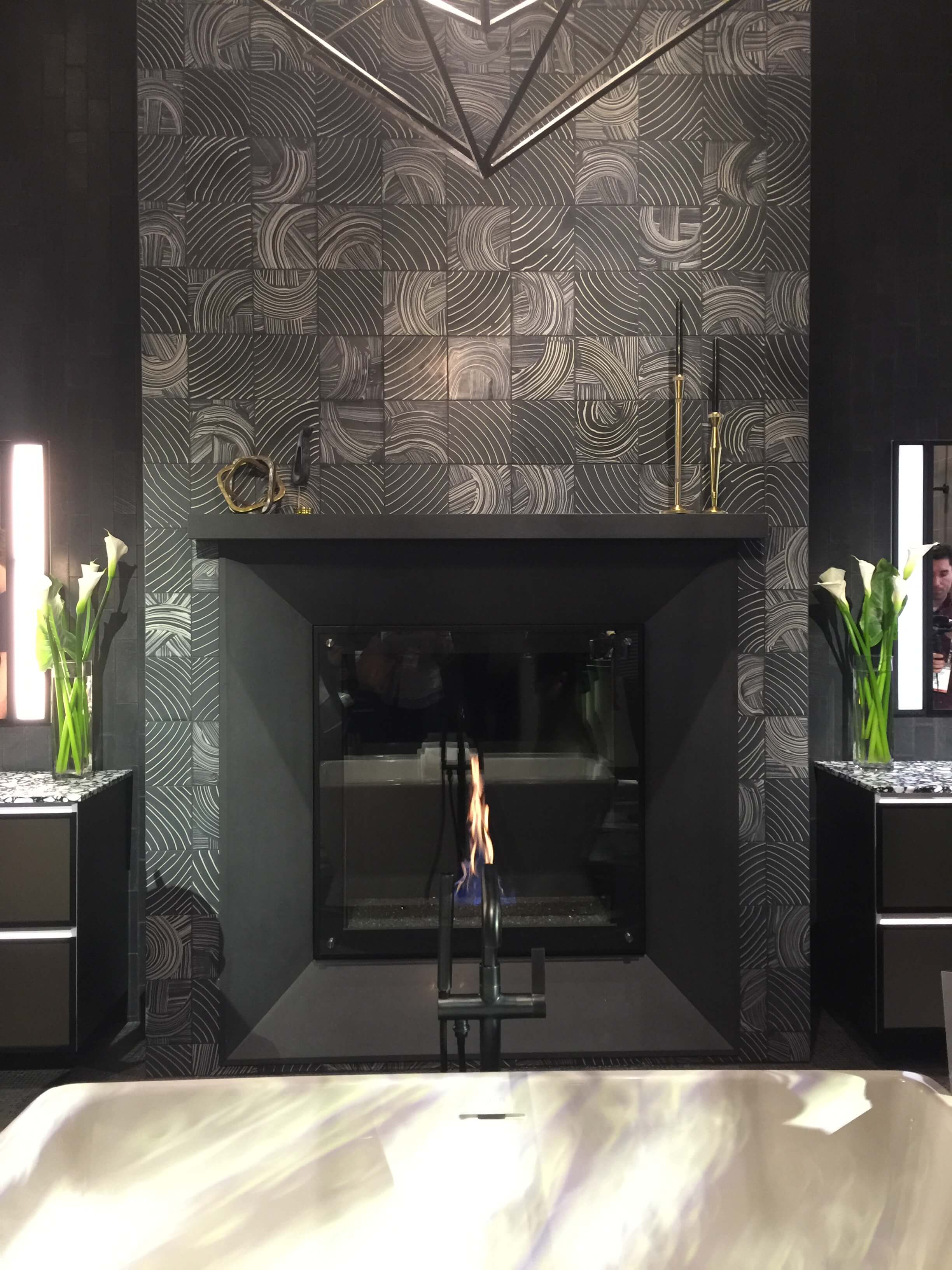 This black and white patterned tile makes a unique statement here on a fireplace in the Ann Sacks booth. Almost looks like swirls from a fingerprint, no? #fireplace #blacktile #blackfireplace #annsacks