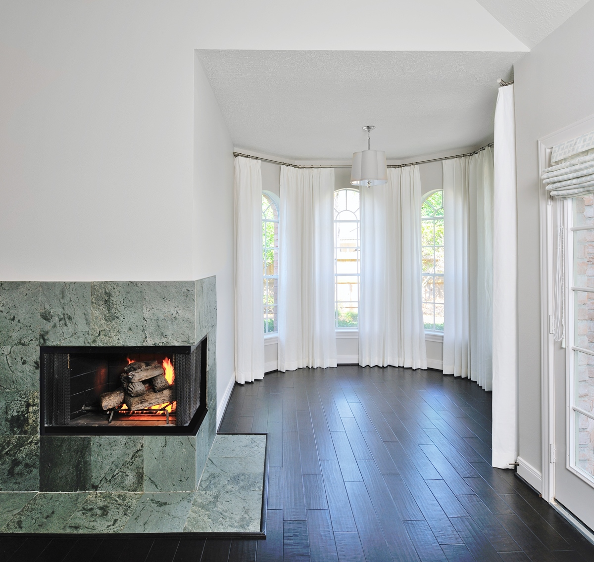 Traversing drapery panels minimized the look of these windows of different sizes in this bedroom alcove - Designer: Carla Aston, Photographer: Miro Dvorscak #windowtreatments #draperypanels #whitecurtains
