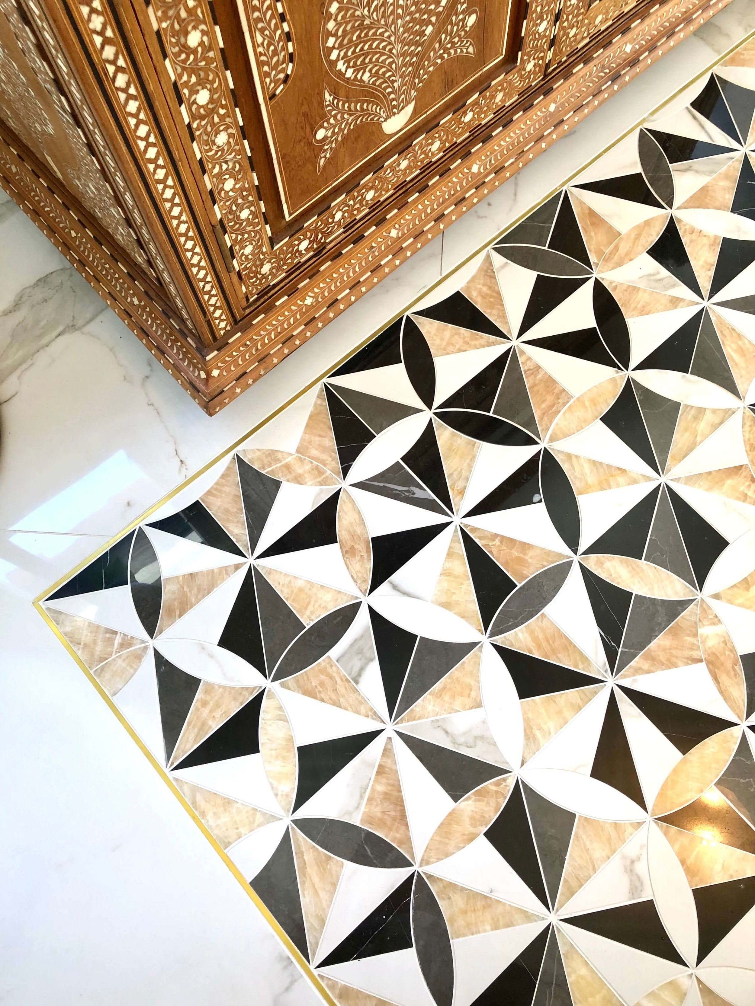 Marble tile inlay pattern with black, white, and brass in master bath flooring - Designer: Parker West Interiors, Pasadena Showcase House of Design