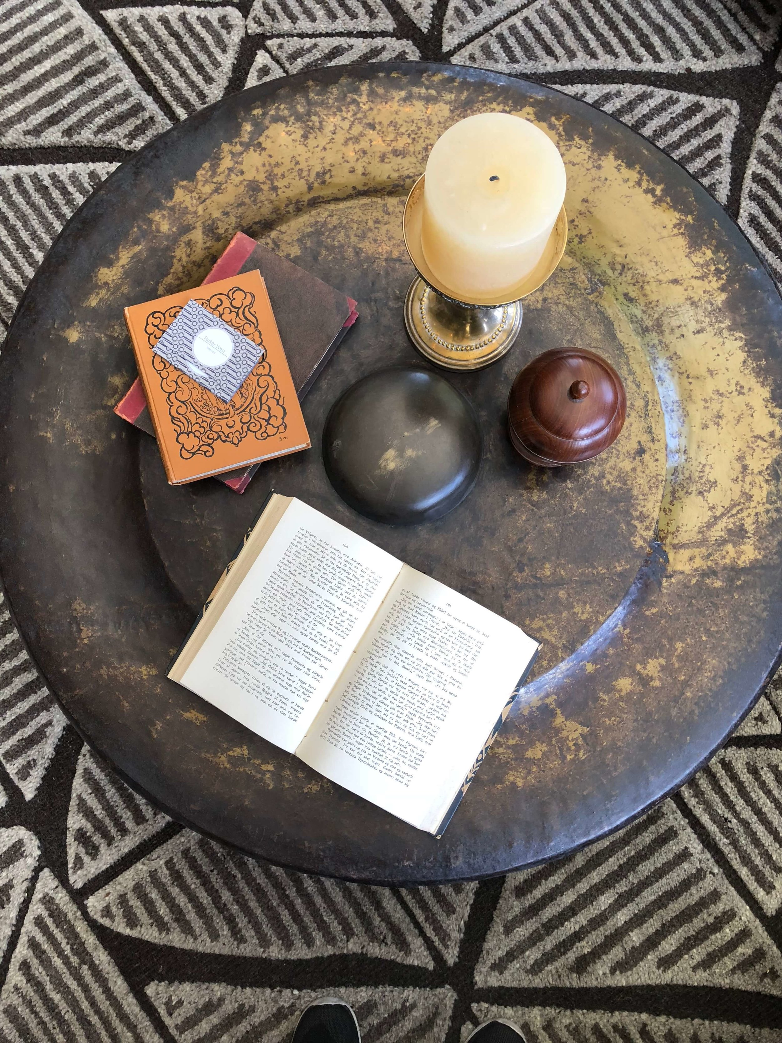 Round metal coffee table with tribal rug and coffee table styling - Designer: Parker West Interiors, Pasadena Showcase House