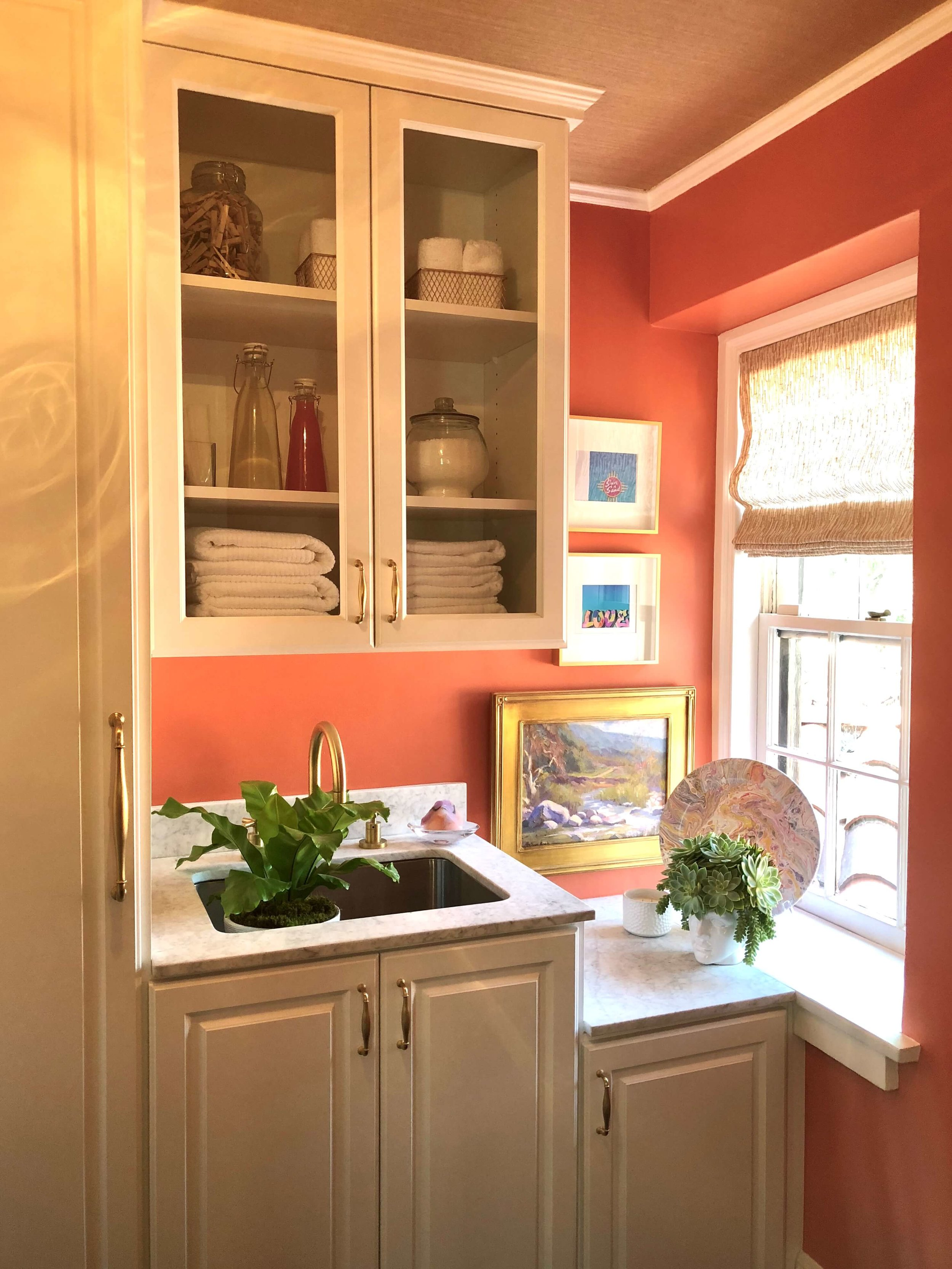 Upstairs laundry room with coral walls and white marble countertops, Designer: Kirsten Acevedo #laundryroom #coral