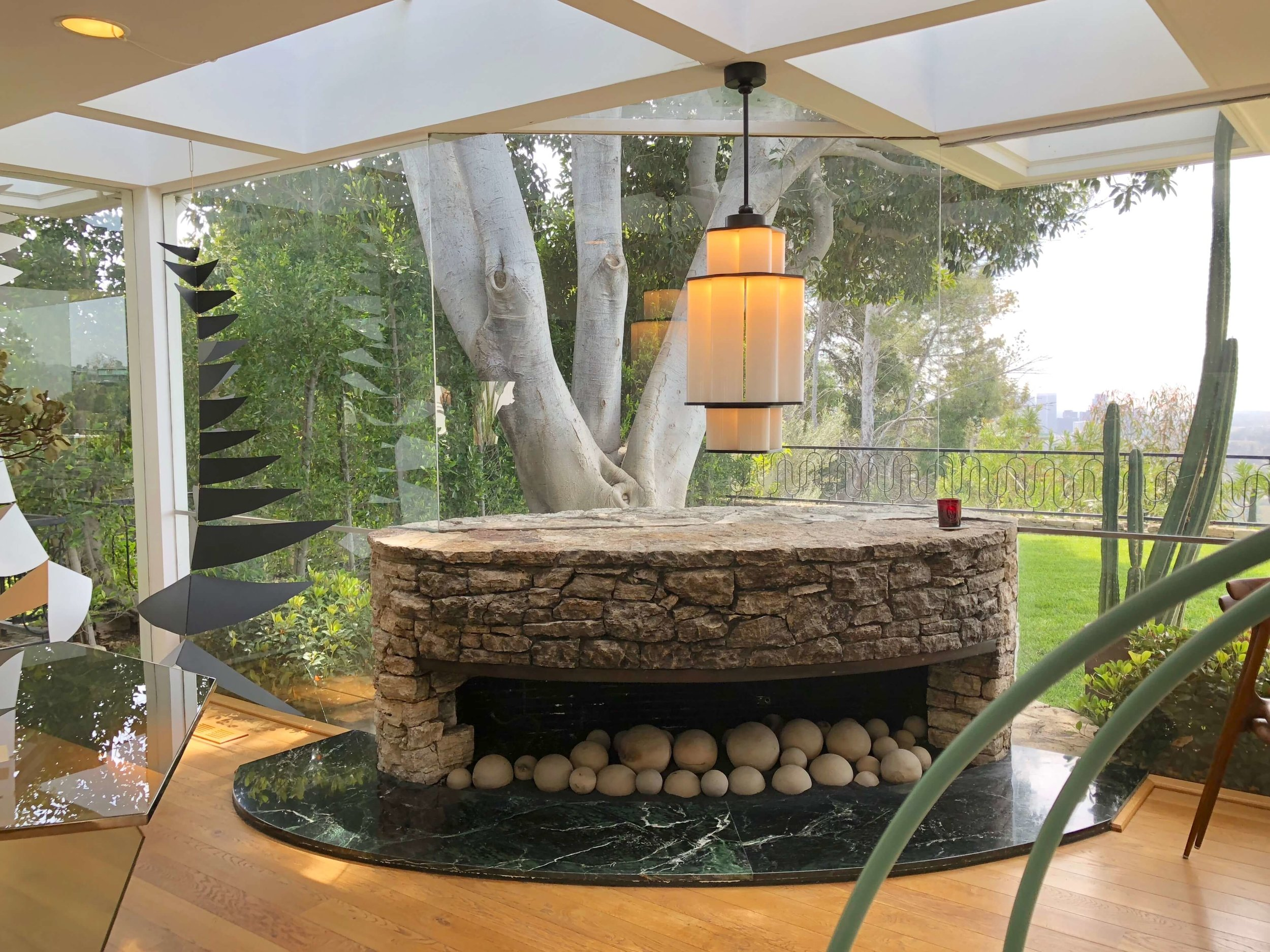 Unusual stone fireplace in oval shape with lighting by Jason Miller at Casa Perfect, Beverly Hills, CA #fireplace #stonefireplace #midcenturymodern