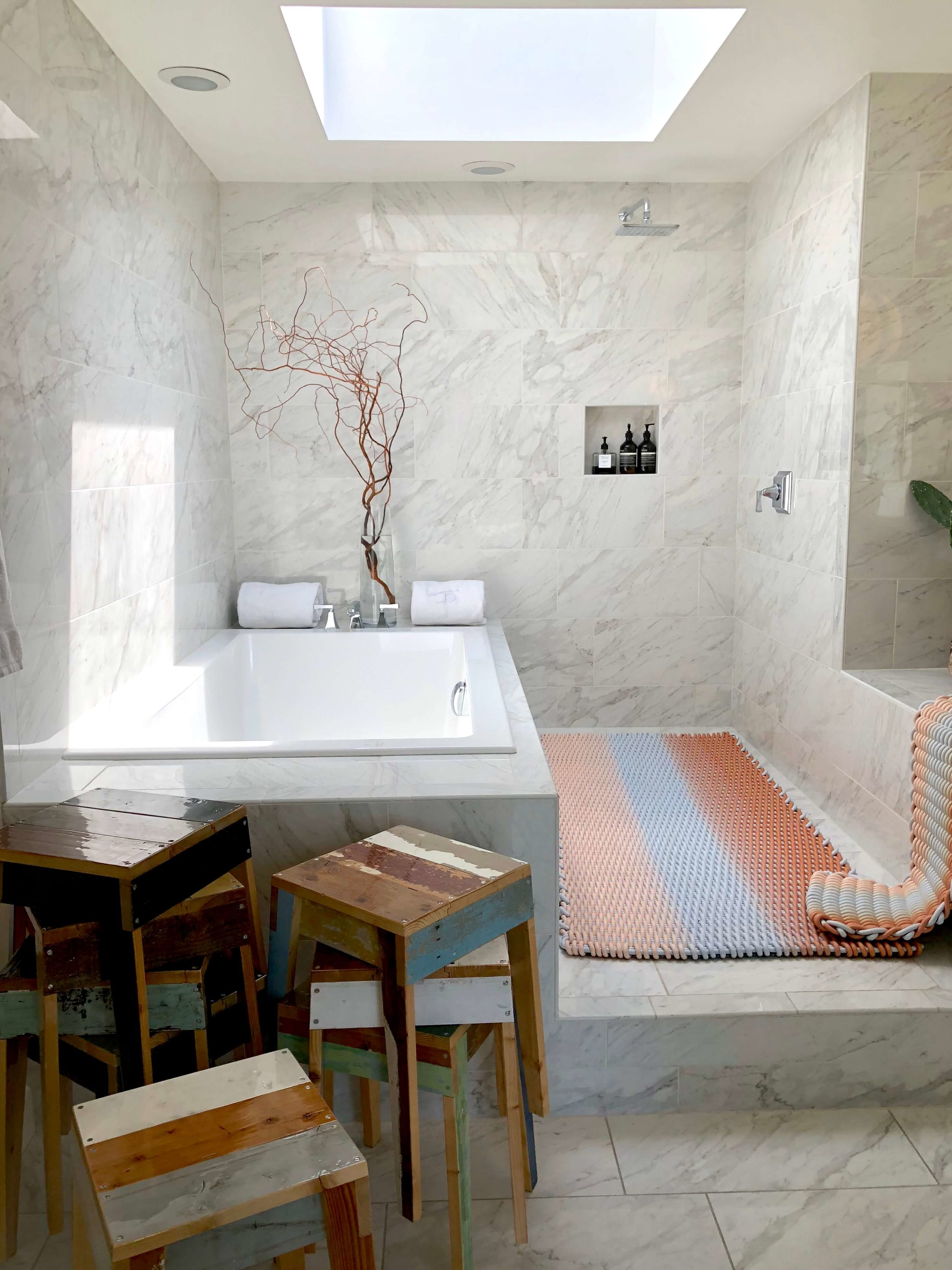 White marble bathroom featuring Shore Rugs and stools by Piet Hein Eek at Casa Perfect #whitemarble #stools #rugs #bathroom