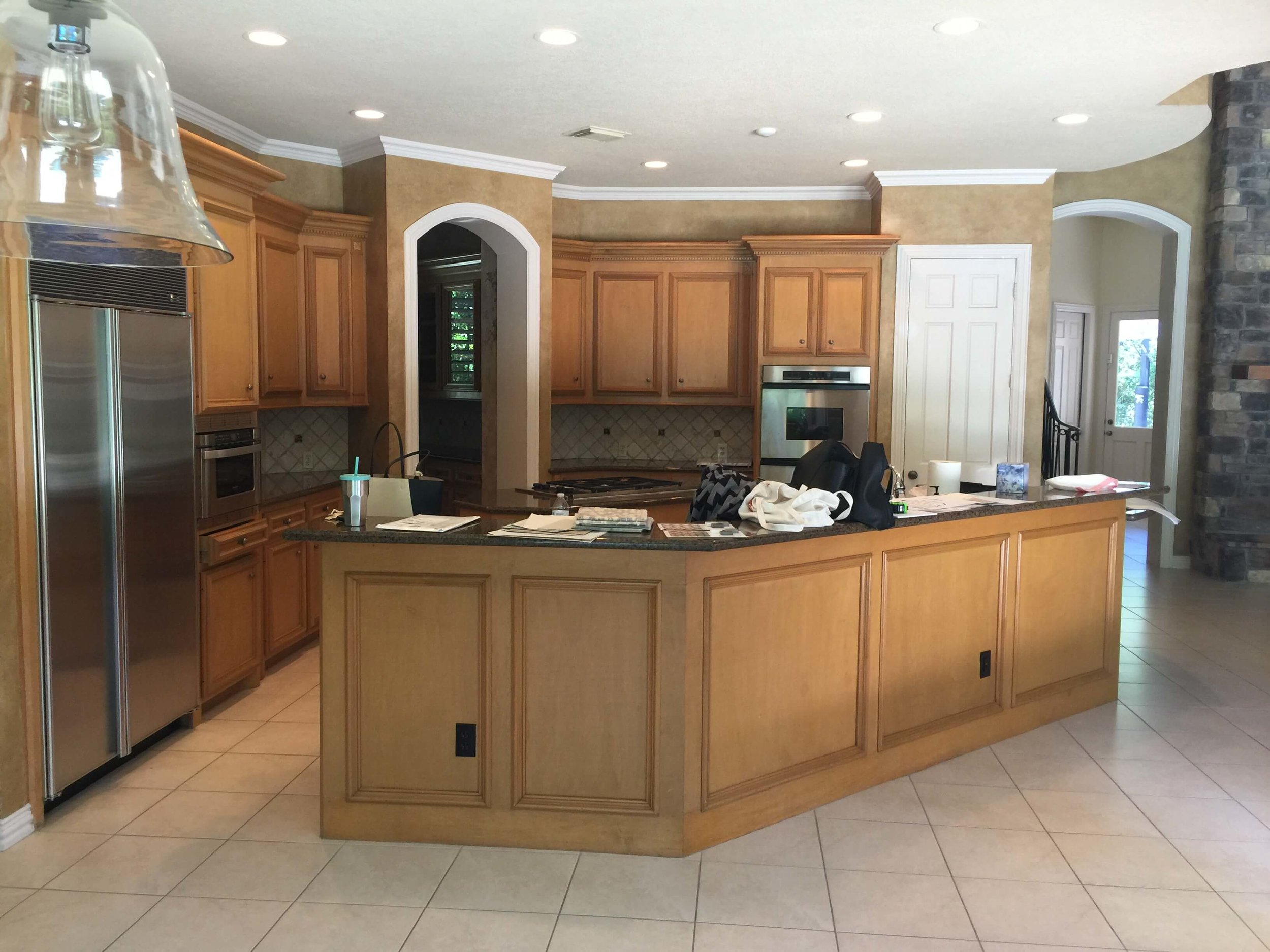 BEFORE - Kitchen with oak cabinets, faux finish walls, and plain tile floor