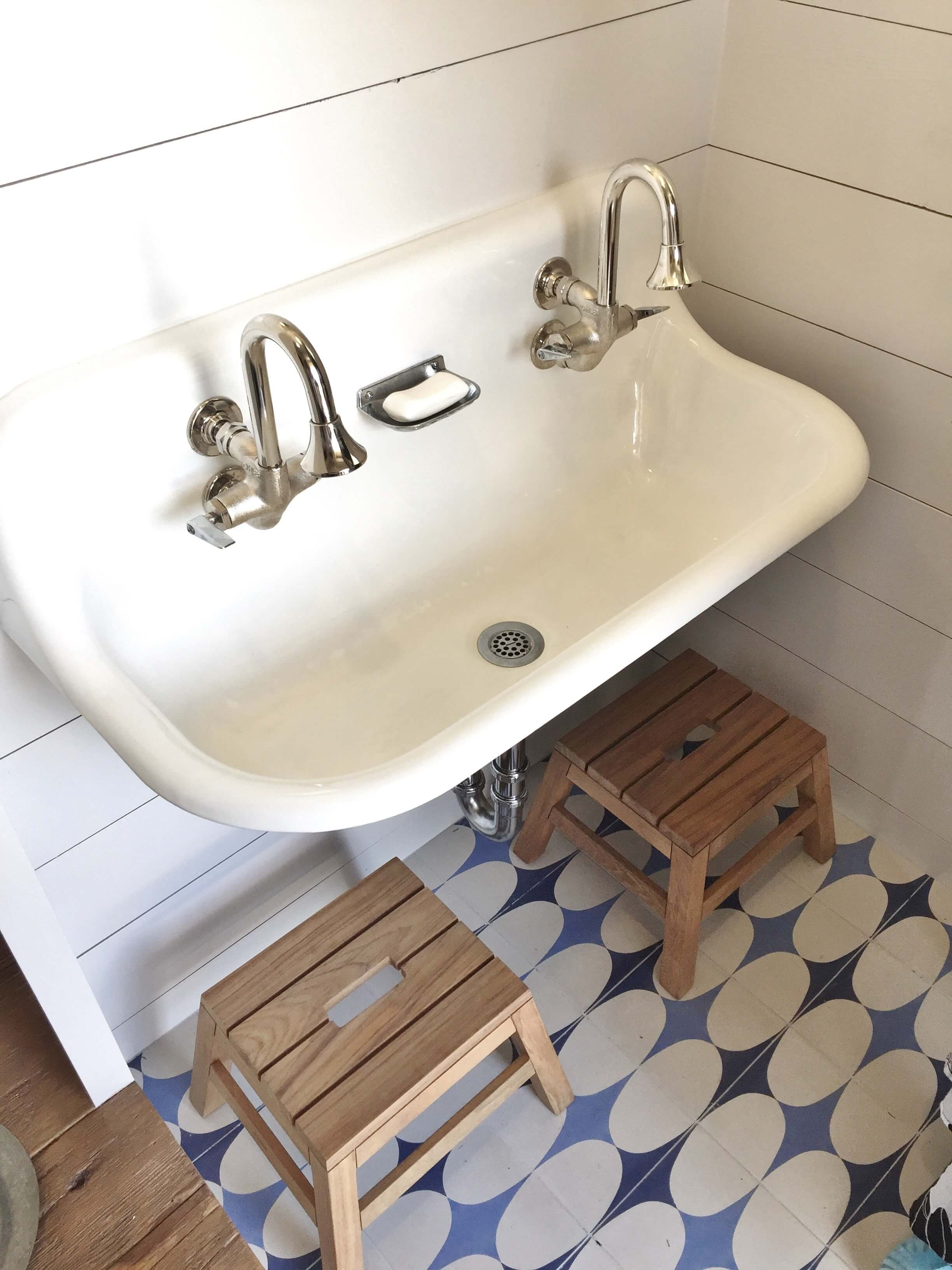 Blue and white cement tiles with vintage wall hung double sink in the poolhouse designed by Jennifer Harbison