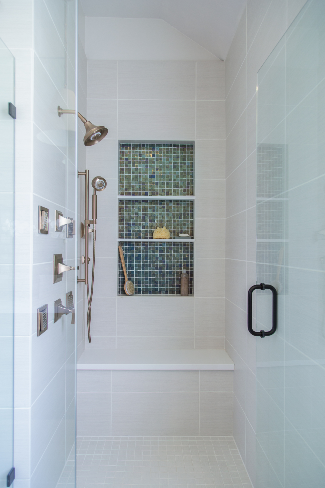 Luxury shower with bench and oversized shampoo niche and body sprays,  Designer: Carla Aston, Photographer: Tori Aston