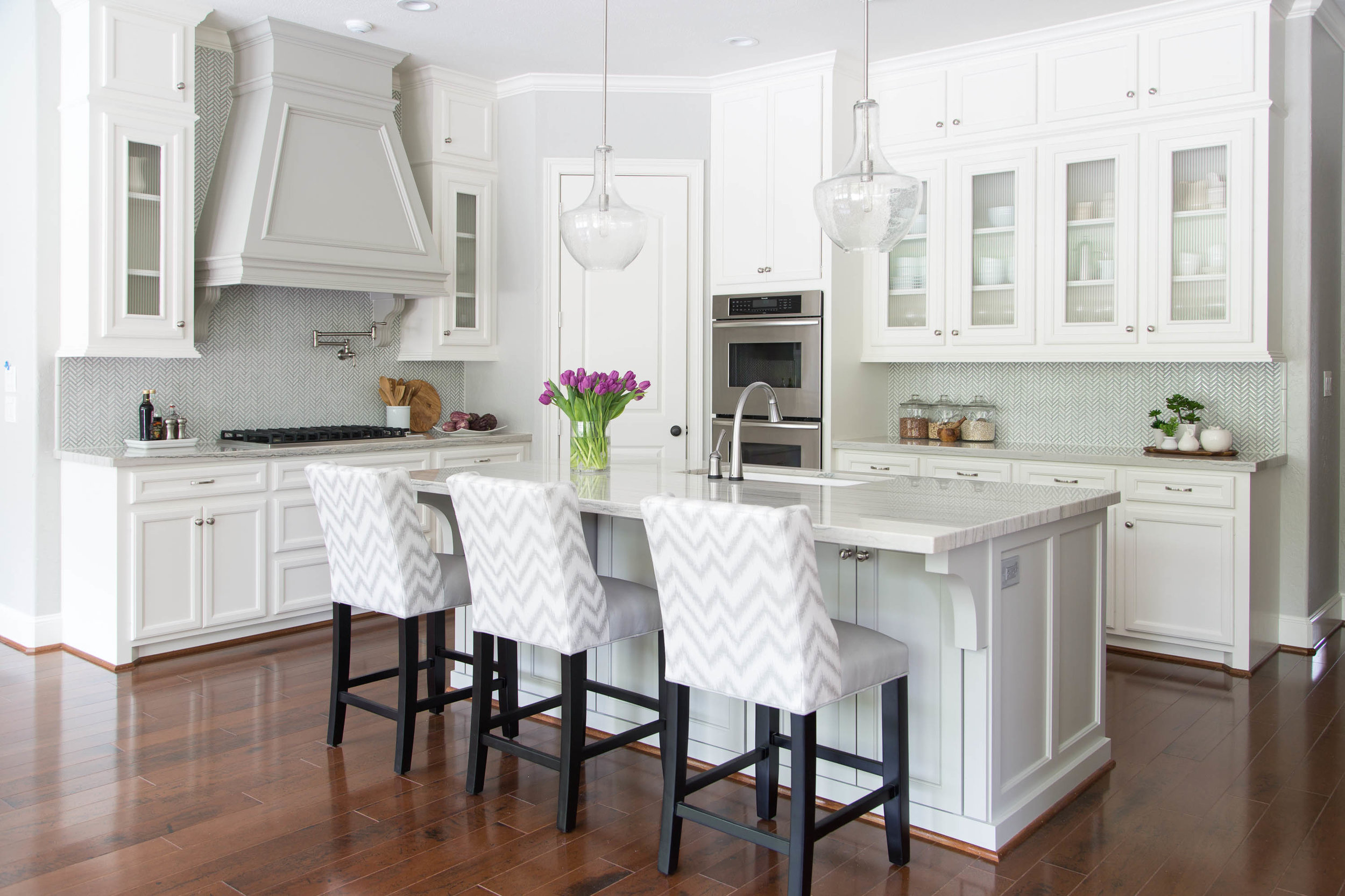 Wood floors add warmth to this white and gray kitchen | Designer: Carla Aston, Photographer: Tori Aston #whitekitchen