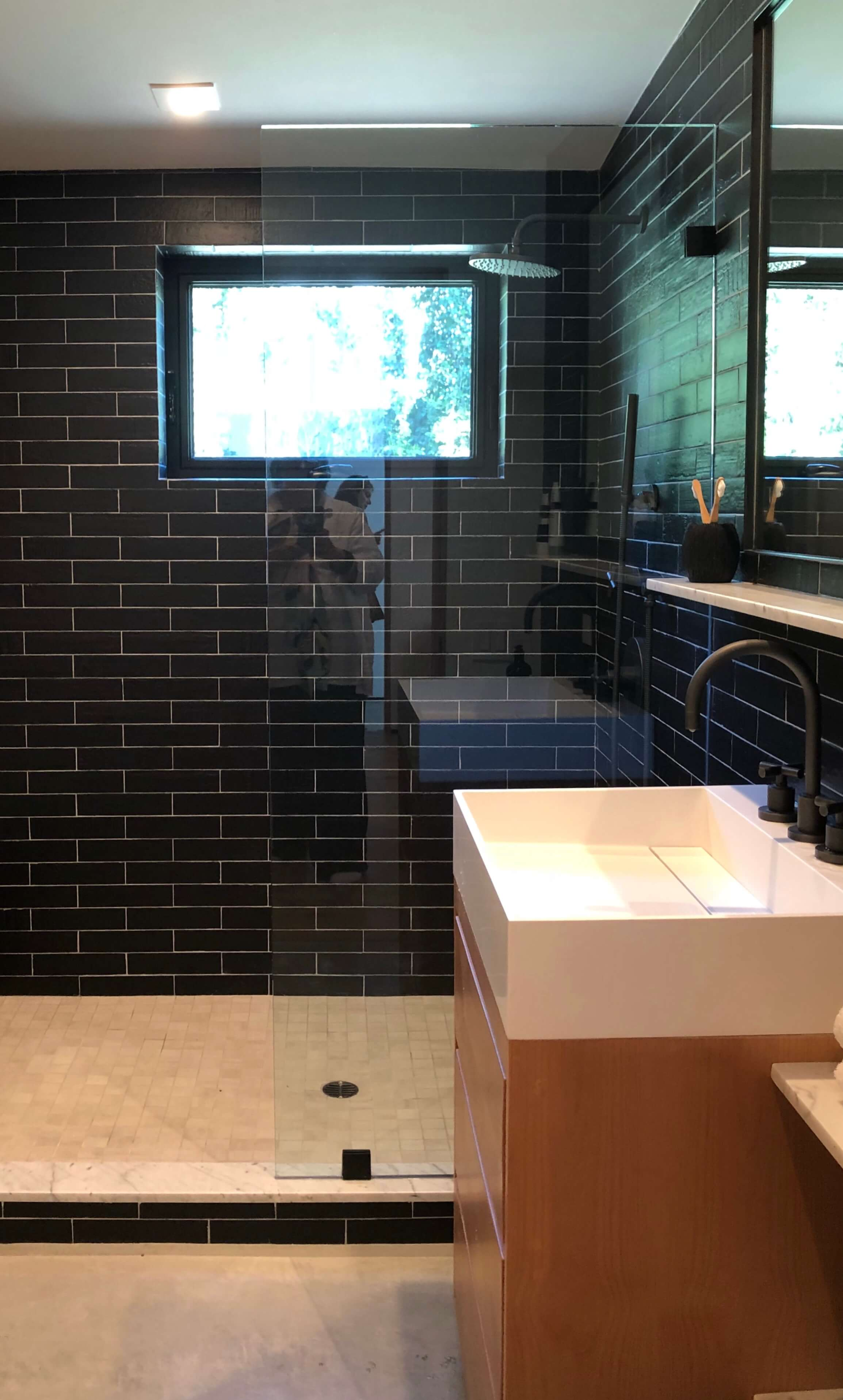 Tile runs through the glass shower wall to visually expand the space, Designer: Vitus Matare | See more about this  comtemporary home here.