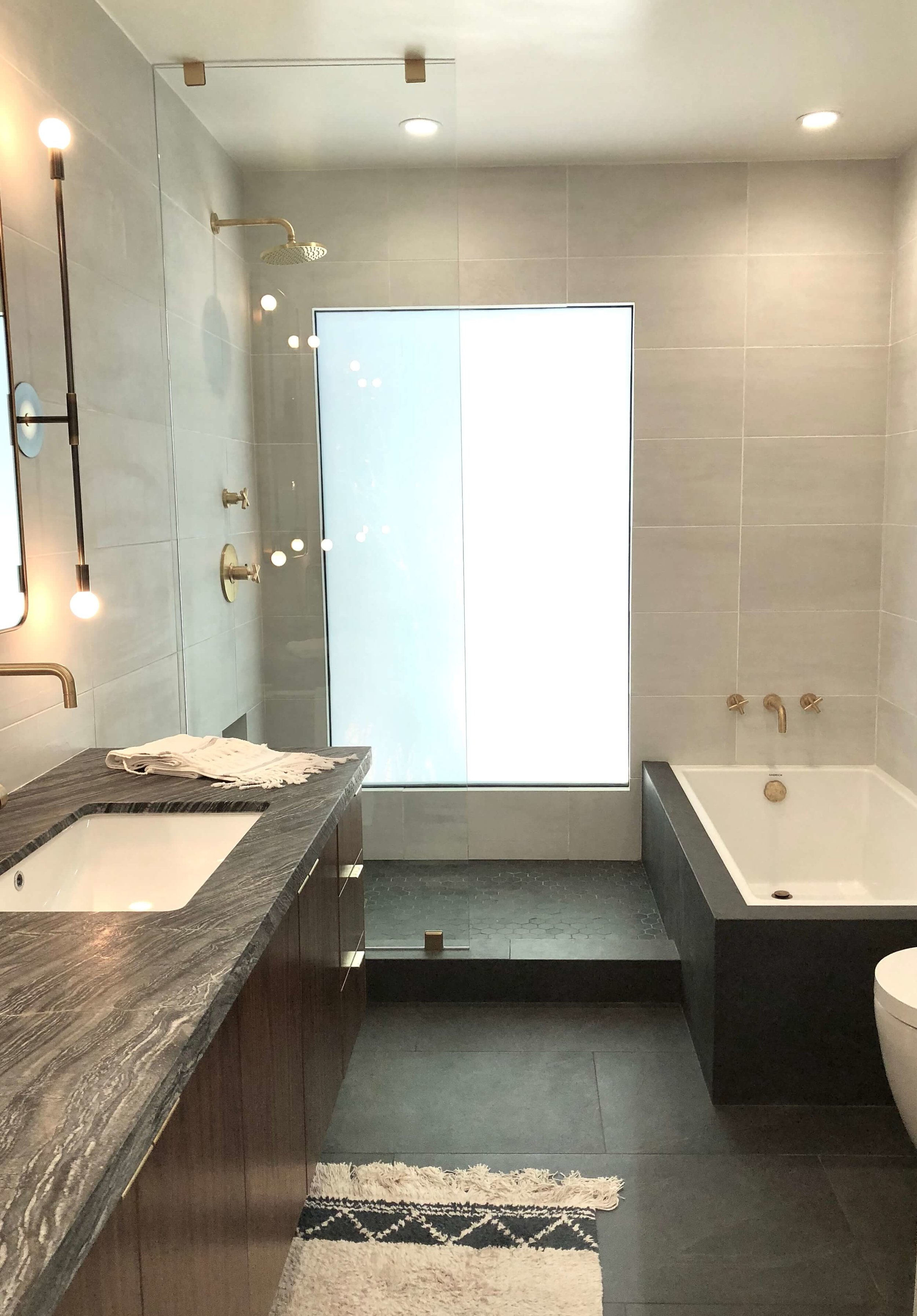 Tile runs through glass shower enclosure | Assembledge Architects | More on this  contemporary home here.
