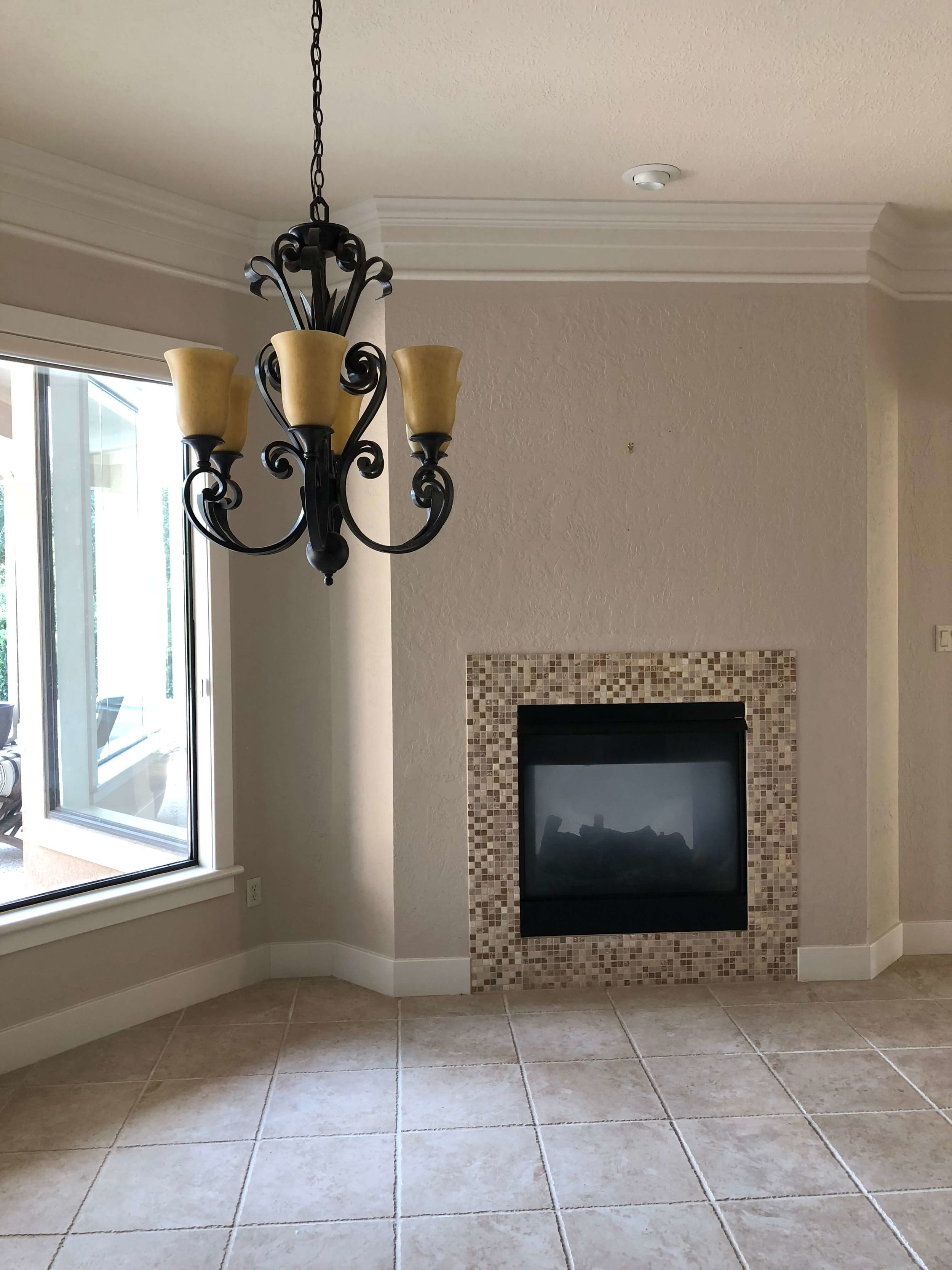 BEFORE REMODEL - Heavy, Tuscan style lighting and a busy tile surround date this breakfast room area just opposite the kitchen #breakfastroom #fireplace