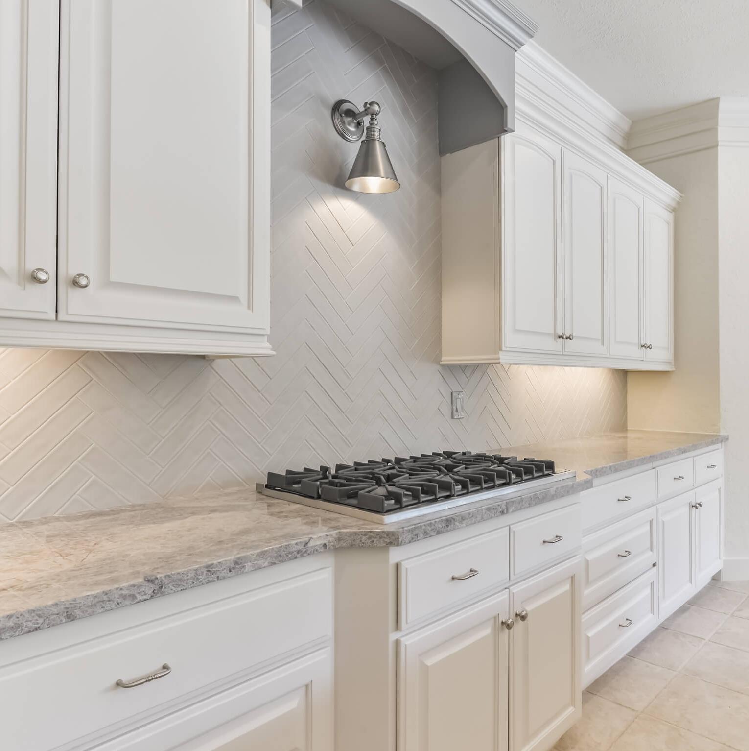 AFTER KITCHEN REMODEL - New countertops, backsplash, paint, cabinet pulls, lighting | Carla Aston, Designer #remodelingideas #remodel #kitchenremodel #herringbonebacksplash #grayandwhitekitchen