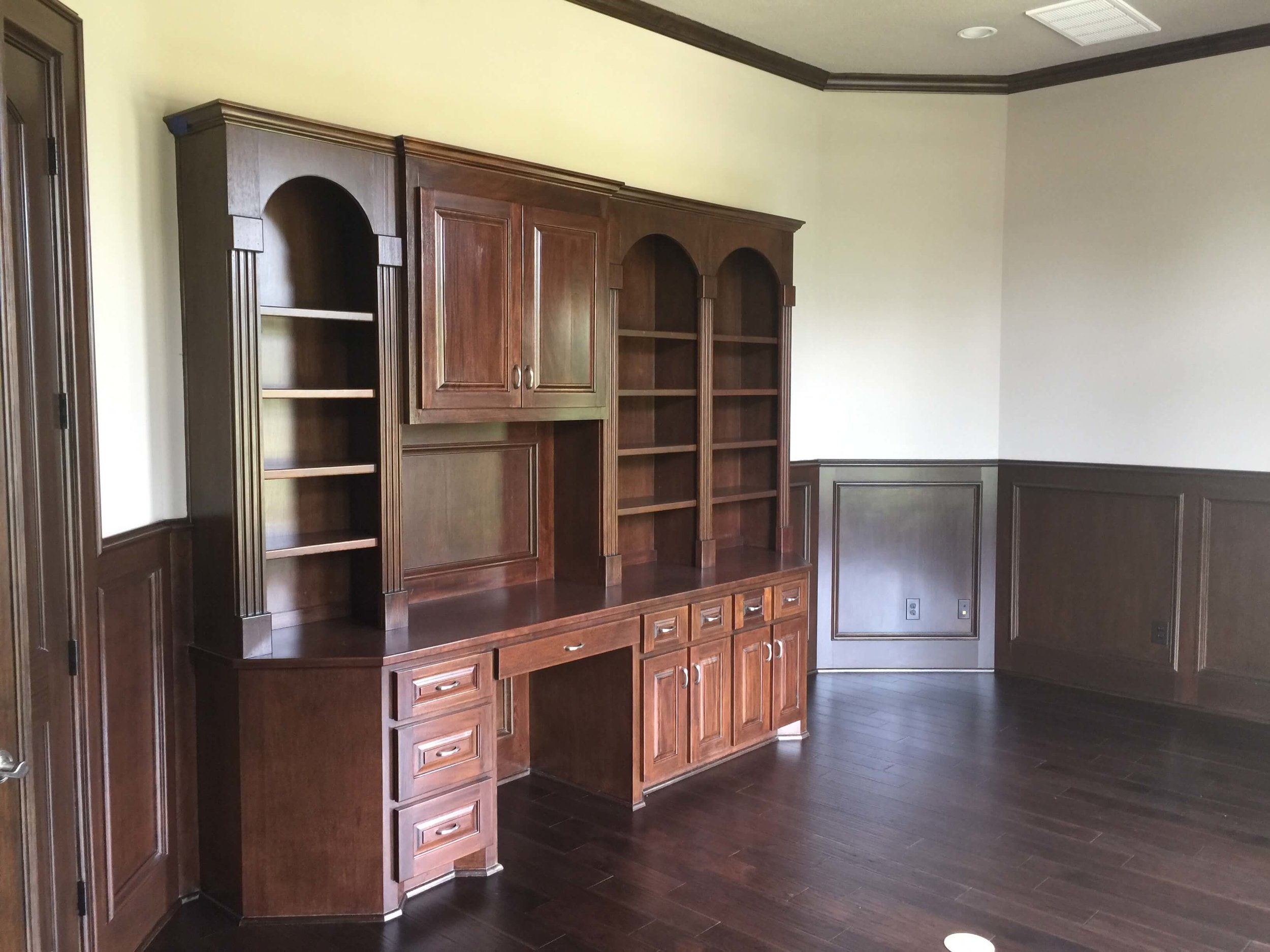 BEFORE - Home office with dark wood paneling and cabinetry