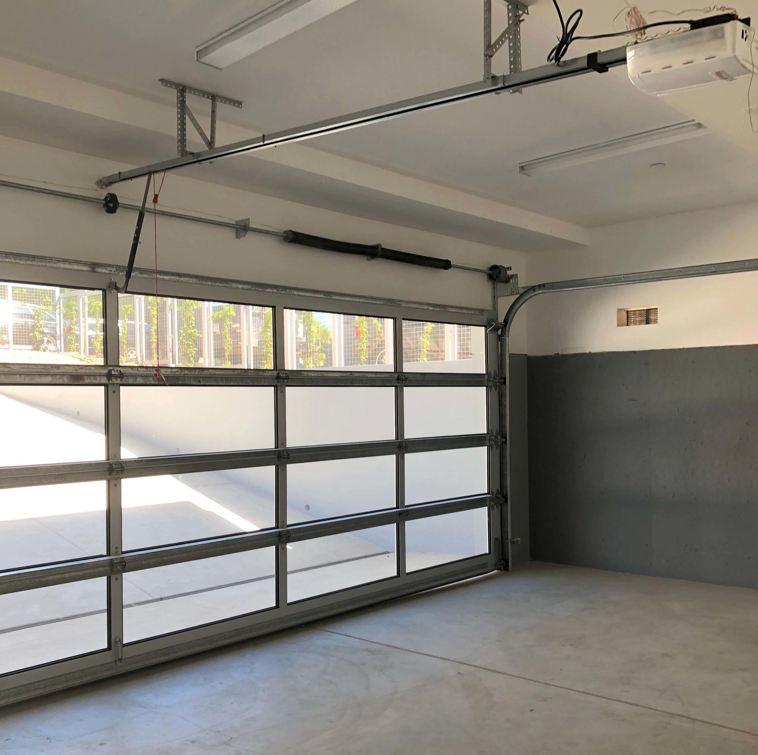 Garage, below the patio, with glass door, gray painted interior |California contemporary design - Dwell on Design's Malibu Home Tour, Designer: Vitus Mitare #contemporaryarchitecture #garage