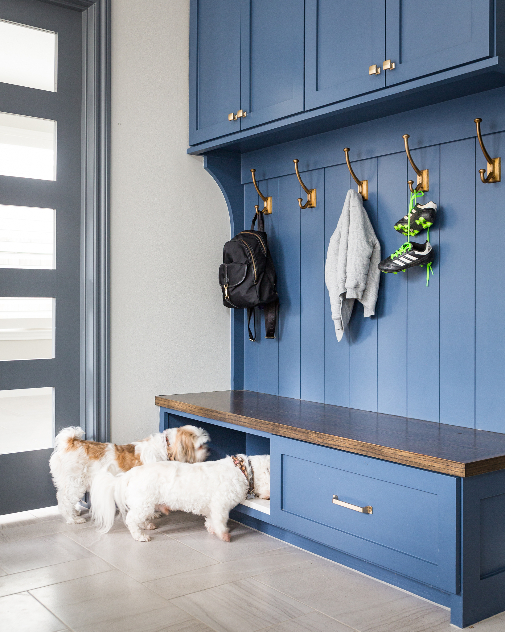BEFORE AND AFTER - A navy and white kitchen remodel w/ mudroom bench, dog feeding station | Carla Aston, Designer | Colleen Scott, Photographer #mudroom #dogbowl #bench #cabinetry
