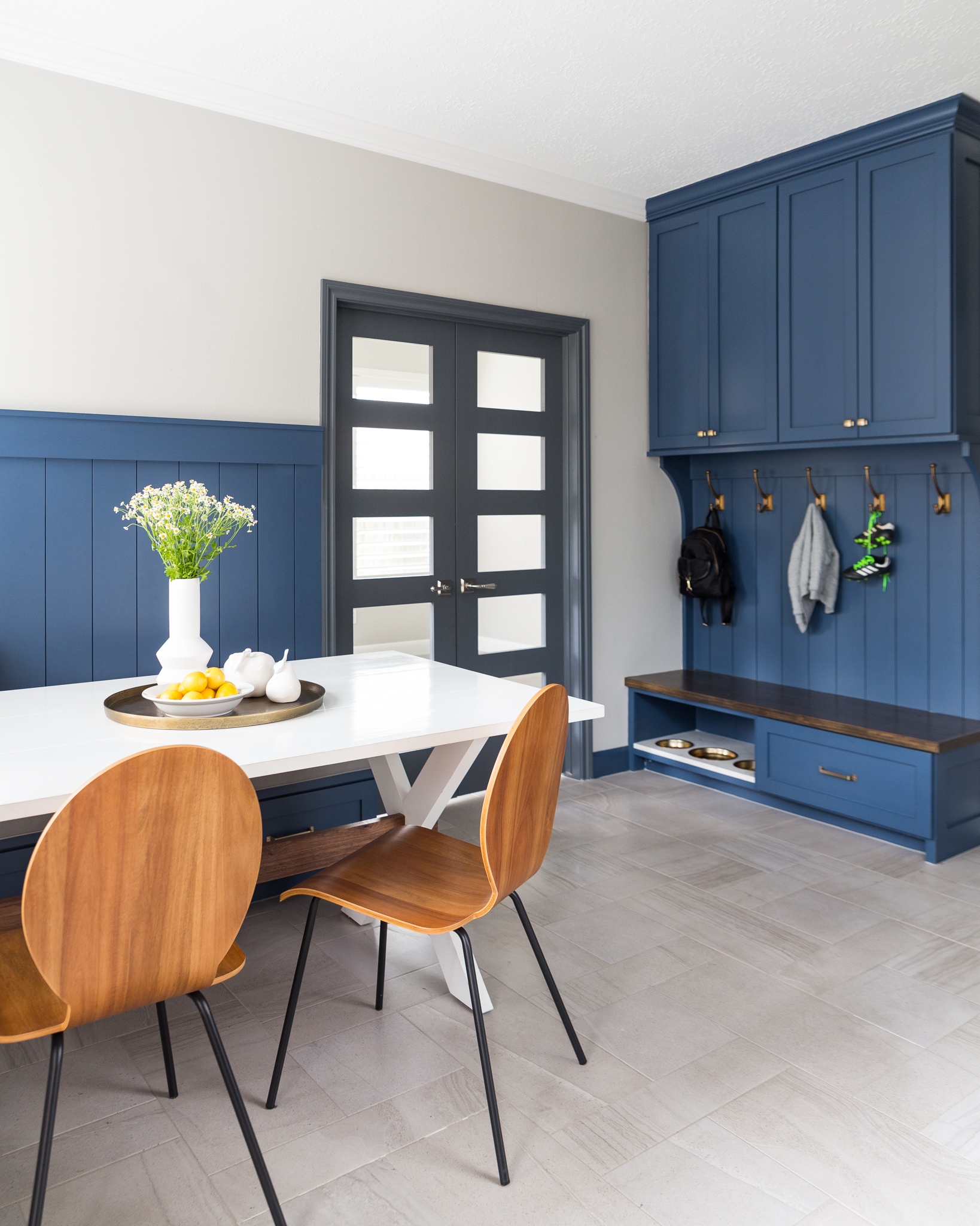 BEFORE AND AFTER - A navy and white kitchen remodel w/ mudroom bench, dog feeding station, breakfast nook | Carla Aston, Designer | Colleen Scott, Photographer #mudroom #dogbowl #bench #cabinetry #breakfastroom