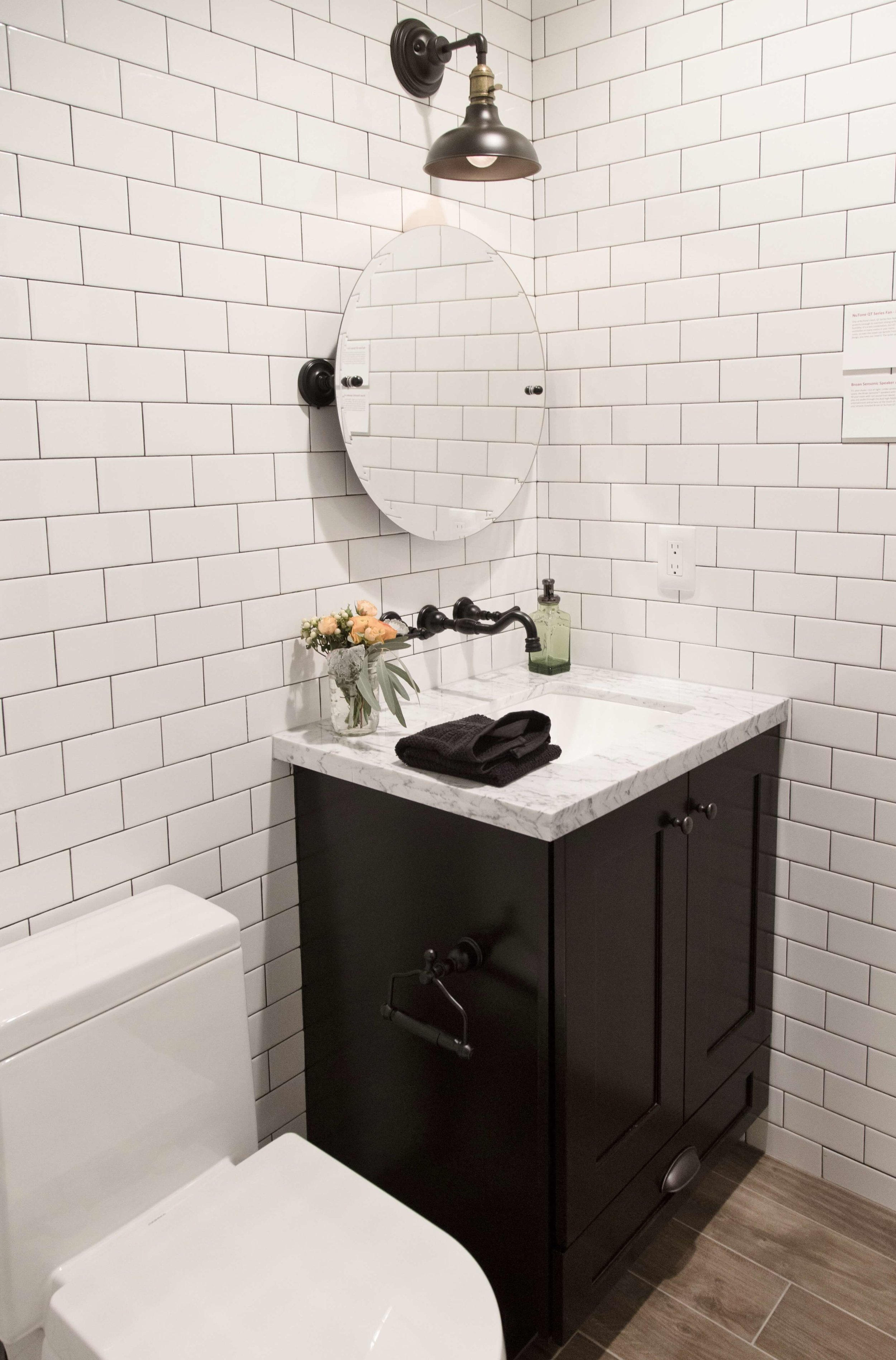 Black faucets in white tiled bathroom | Designer: Bobby Berk, Pardee Homes