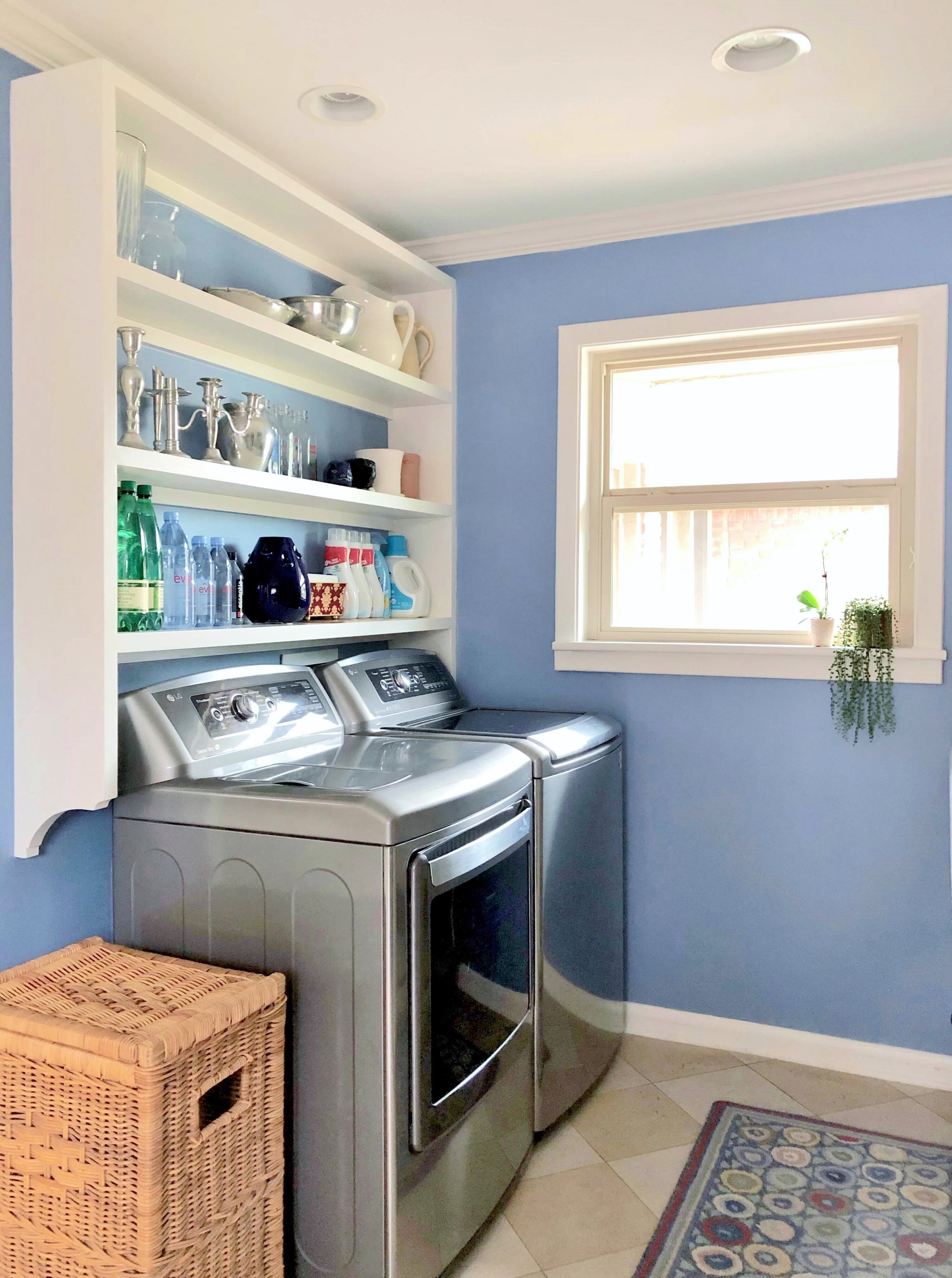 Pretty laundry room in periwinkle blue, bracketed open shelving above | Carla Aston, Designer