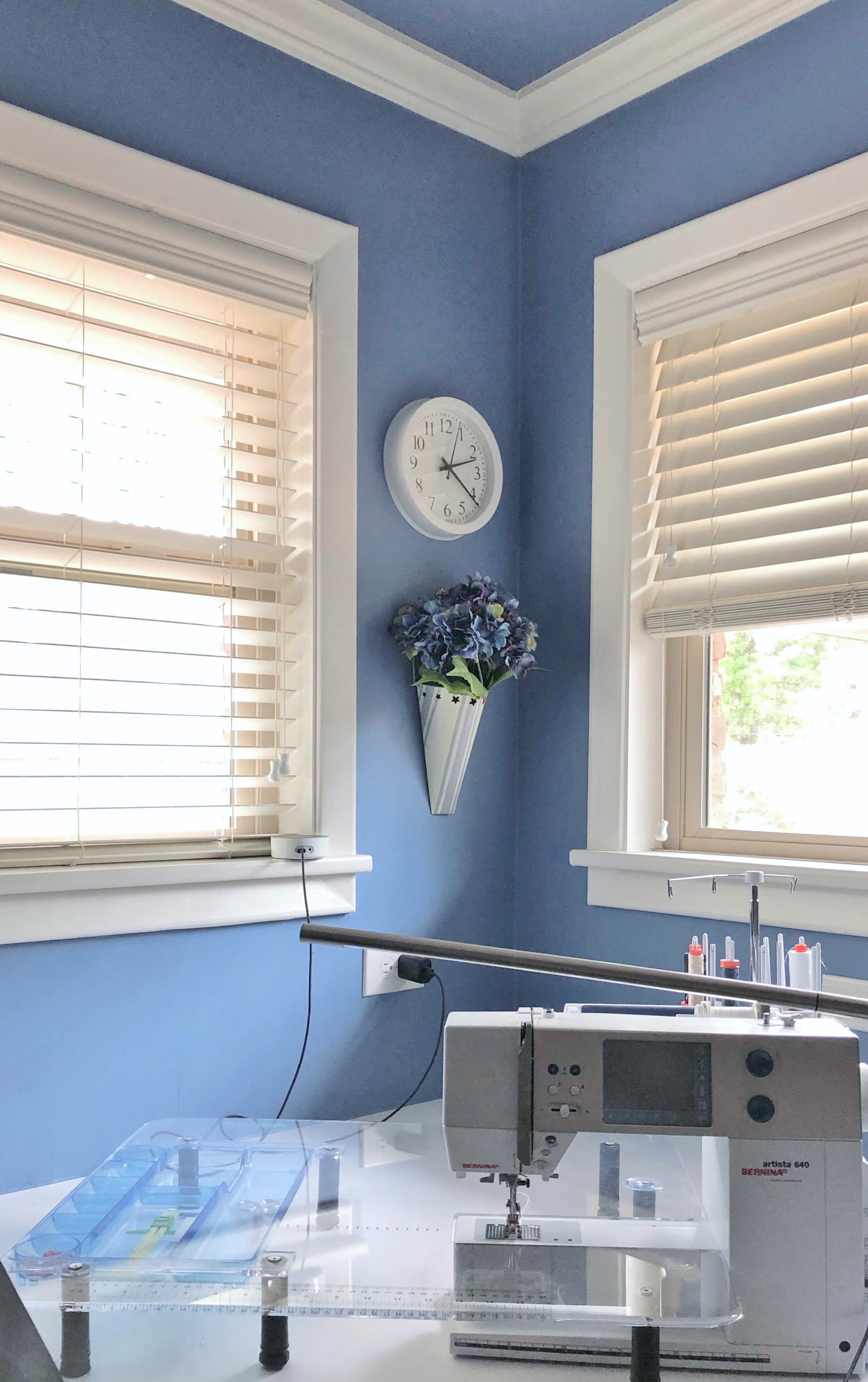 Periwinkle blue sewing room work space at the windows
