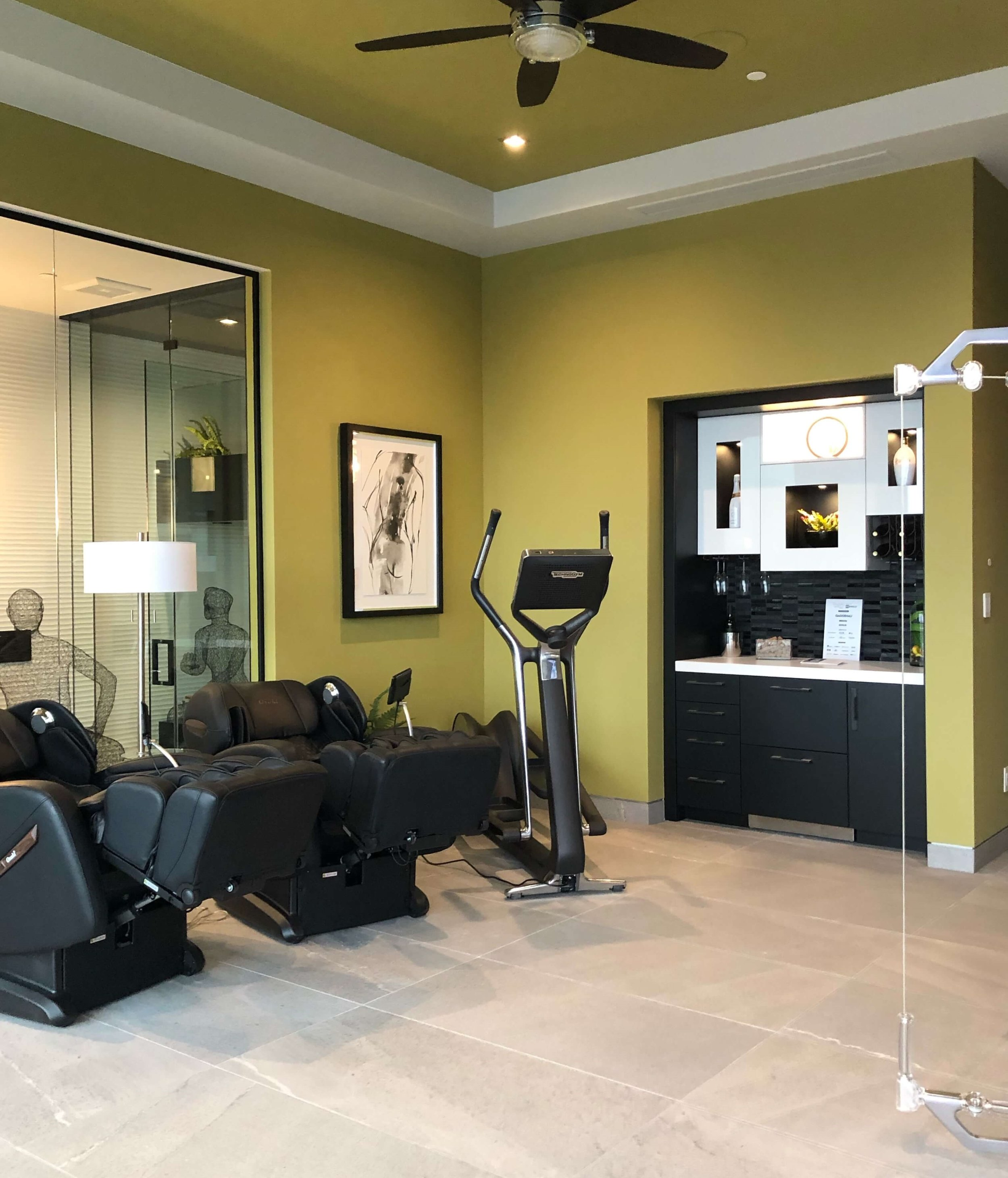 Exercise room equipped with massage chairs, The New American Home Tour 2019 | Designed and built by Sun West Custom Homes  #contemporaryhome #homegym #exerciseroom