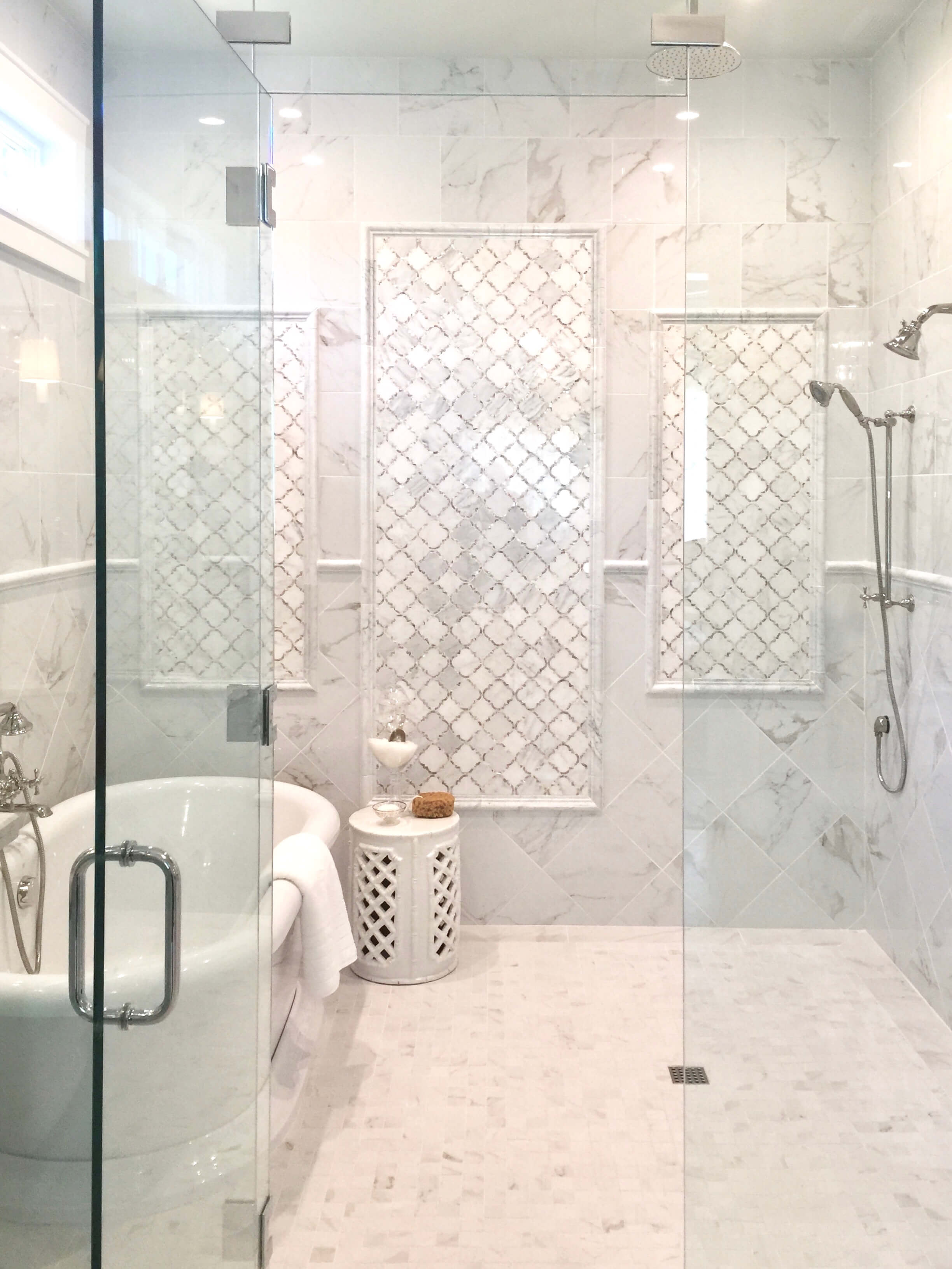 The master bath had a walk-in bathing room with the tub in the enclosed shower area. White marble tile covered the walls and floor. Designed by Chairma Design Group #bathroomdesign #freestandingtub