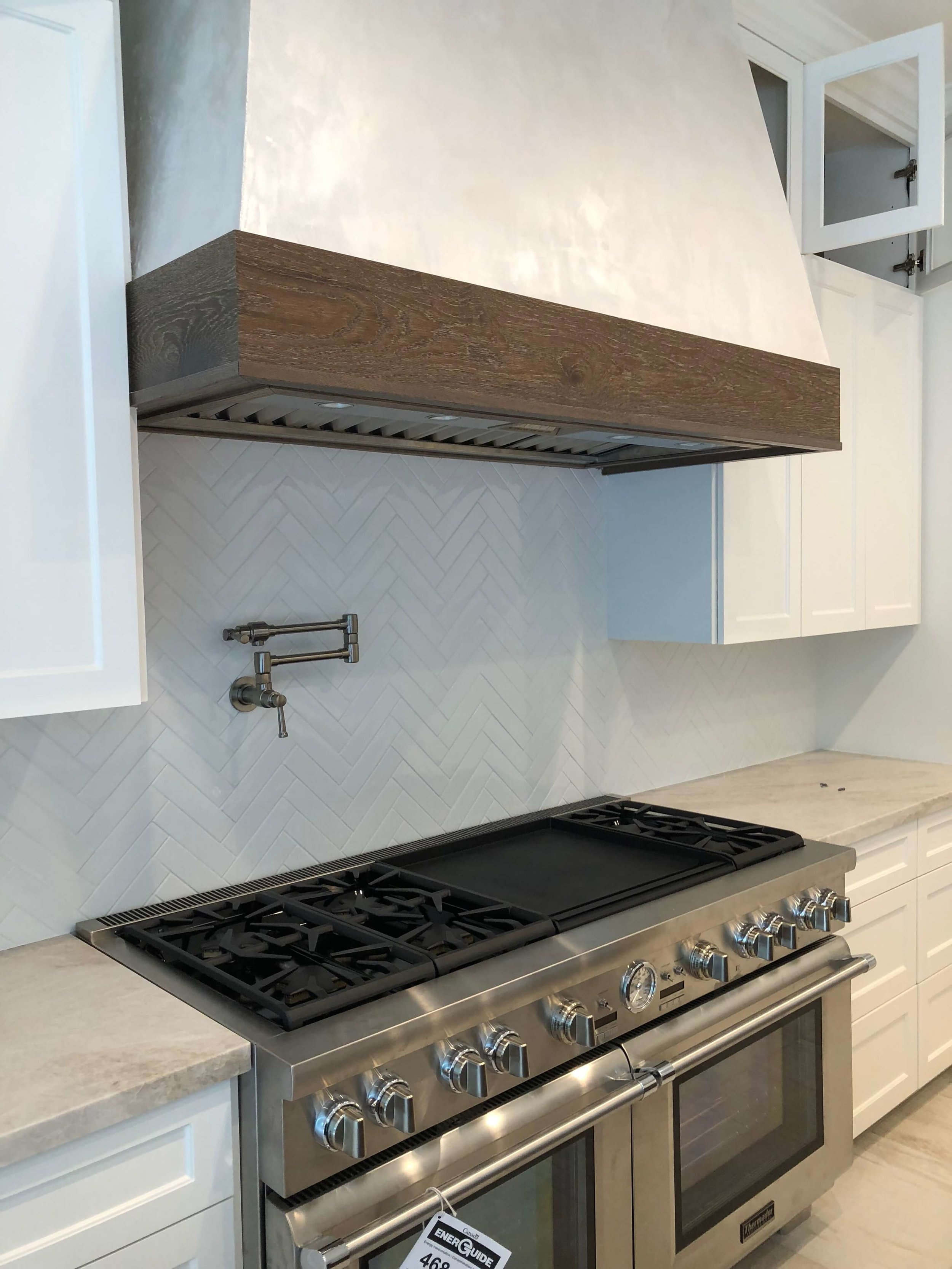 "The 60"" Thermador range is in with the gorgeous herringbone laid tile backsplash and plaster hood with wood trim 