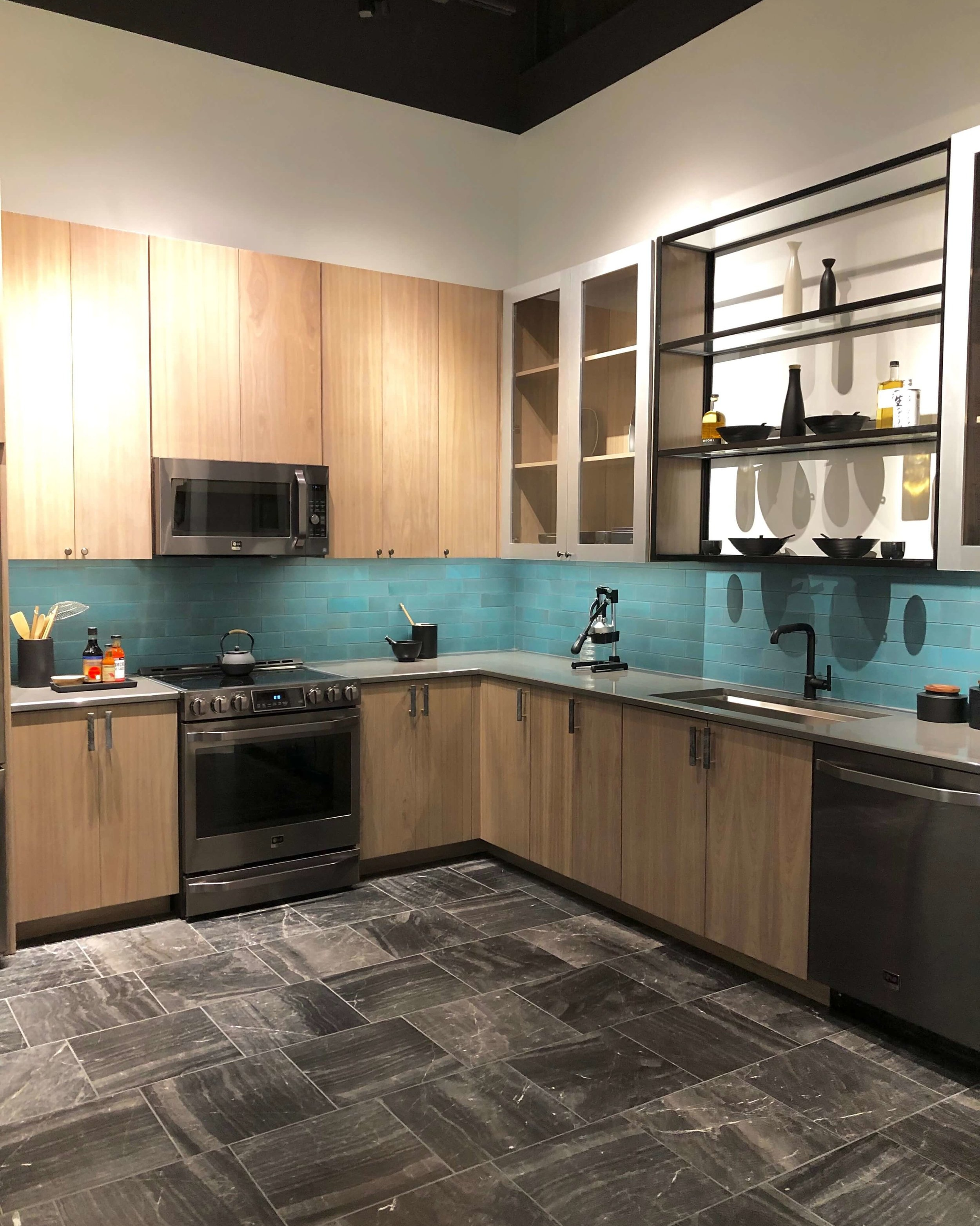 Natural wood cabinetry with black hardware details and turquoise tile backsplash in kitchen with LG Appliances | SKS Appliances Experience and Design Center, Napa