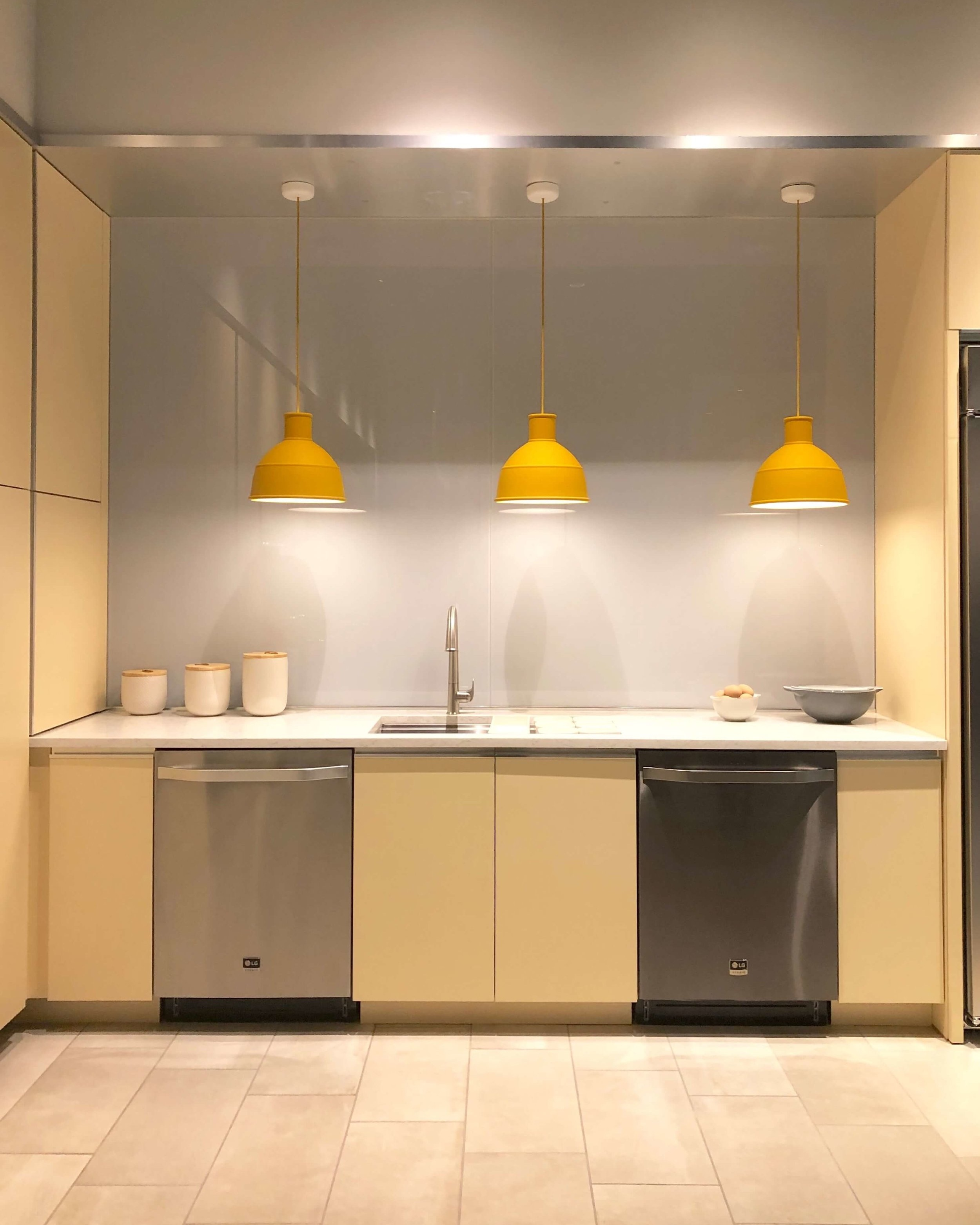 Butter yellow cabinetry and yellow pendants in kitchen w/ LG Appliances | SKS Appliances Experience and Design Center, Napa