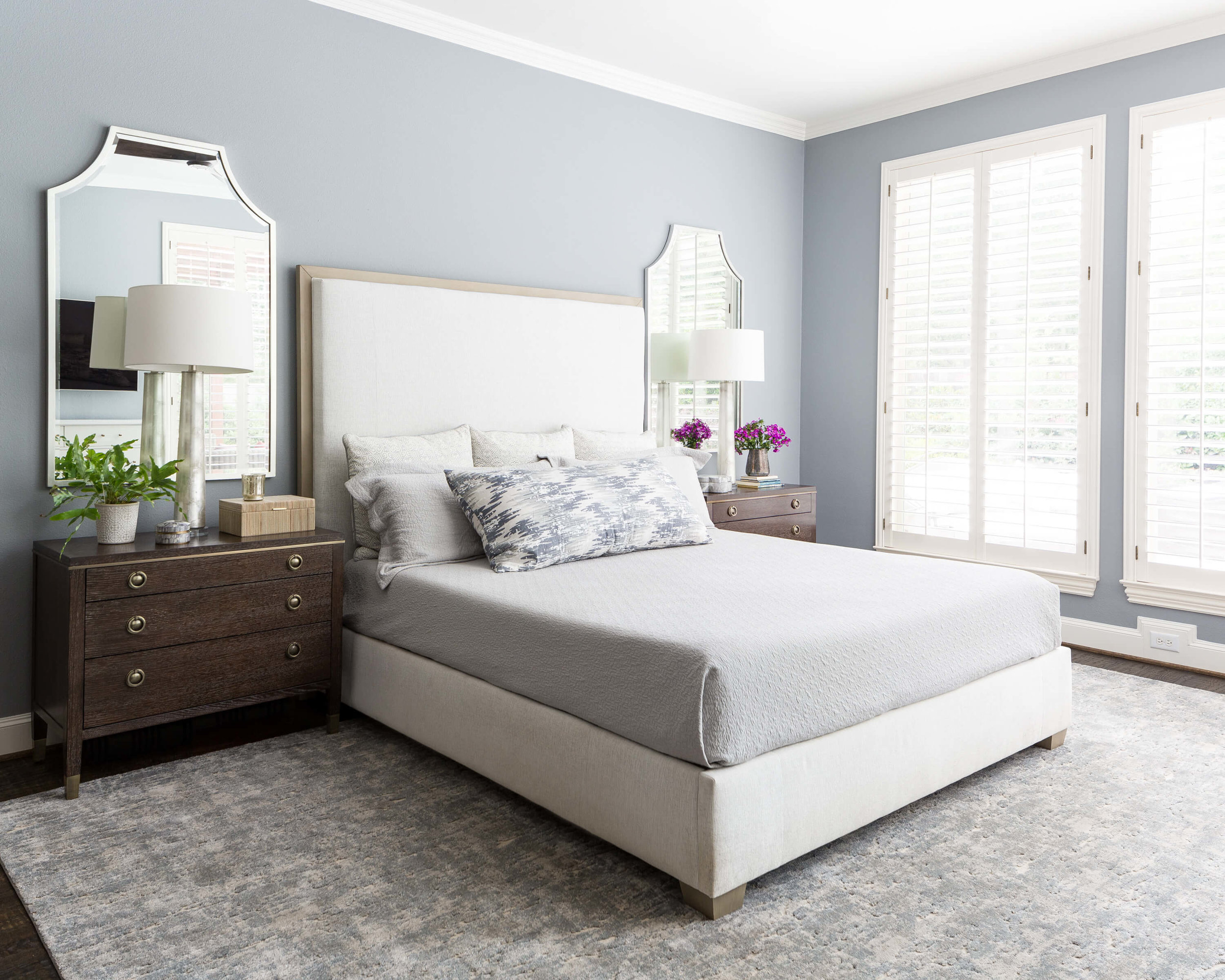 Soothing master bedroom in blue gray color palette with dual mirrors and glass lamps on dark wood nightstands. Carla Aston, Designer | Colleen Scott, Photographer #masterbedroom #nightstand #headboard