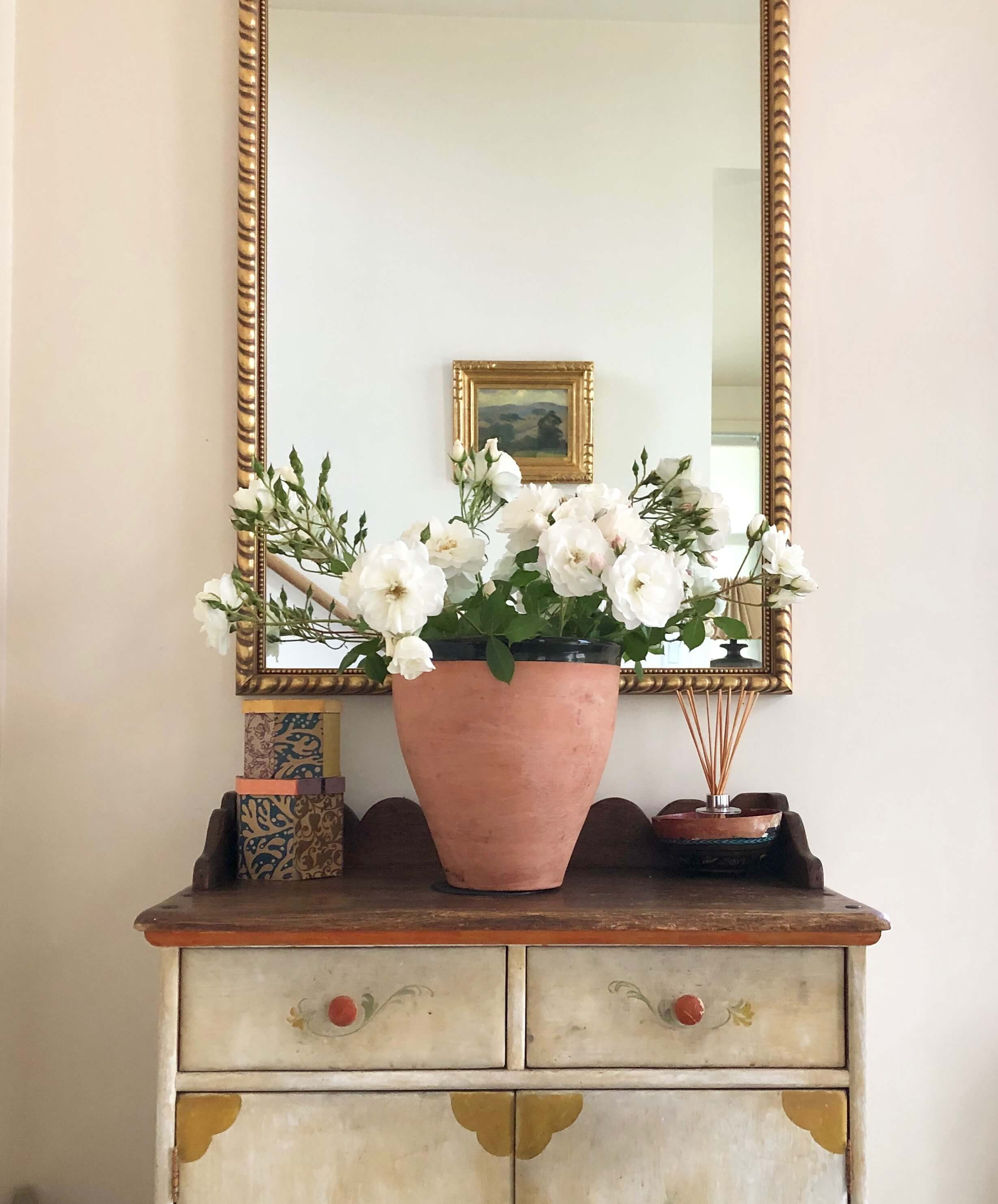 Simple foyer vignette with gilded mirror, painted rustic console and an abundance of white roses. #airbnb #winecountry