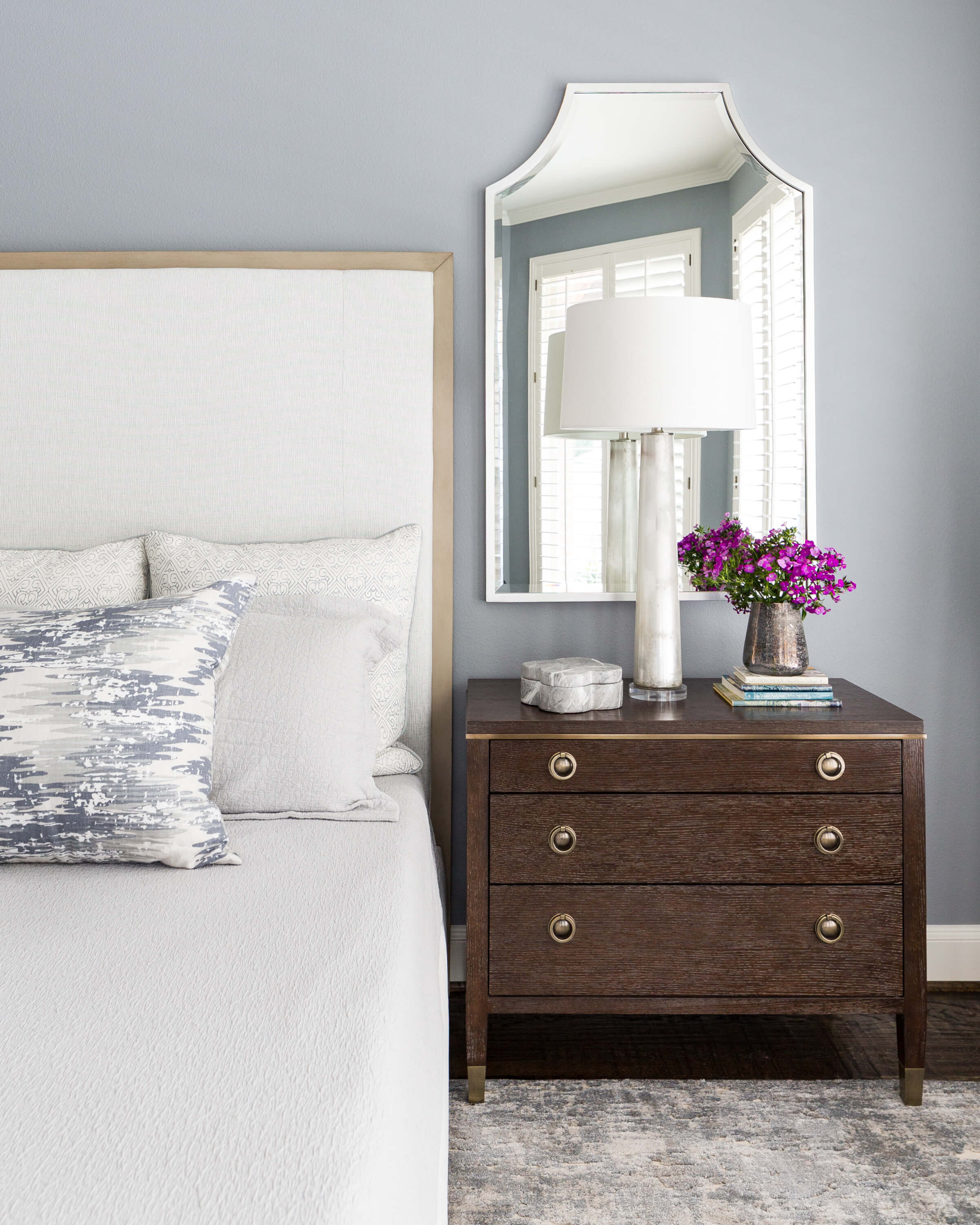 Soothing master bedroom in blue gray color palette with mirror and glass lamp. Carla Aston, Designer | Colleen Scott, Photographer #masterbedroom #nightstand #headboard